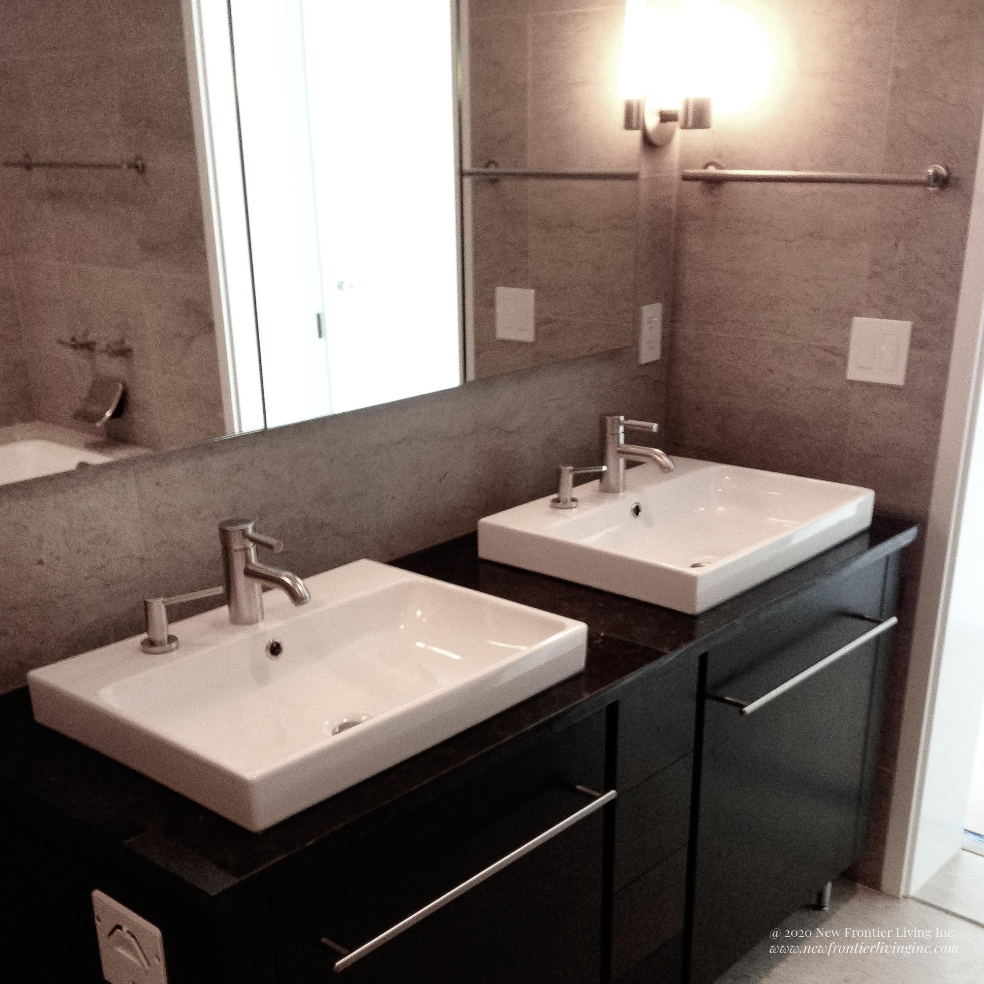 Cream brown bathroom installed by NFL Inc. with two sinks and vanities and a mirror