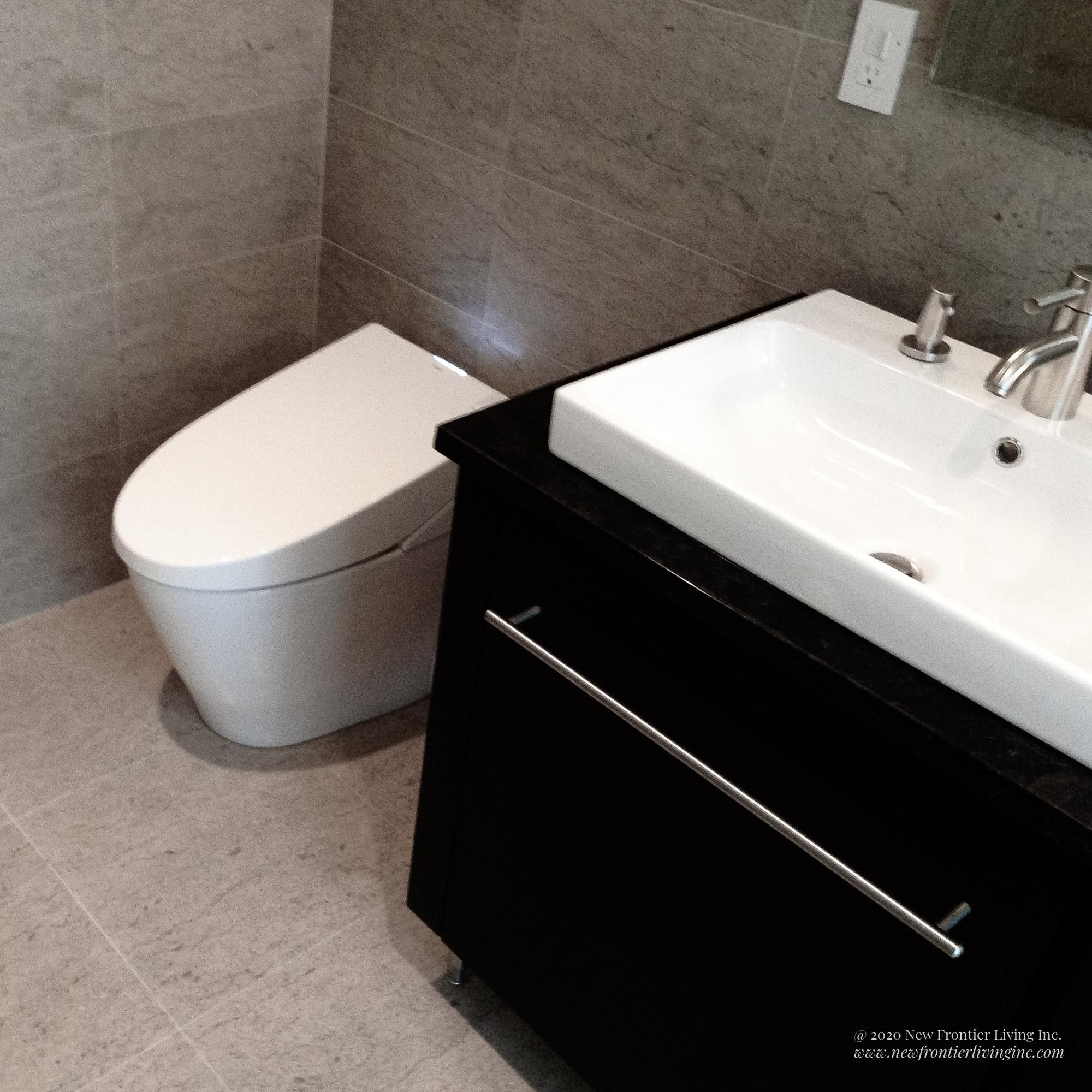 Cream brown bathroom installed by NFL Inc. one sink and vanity and toilet on the left
