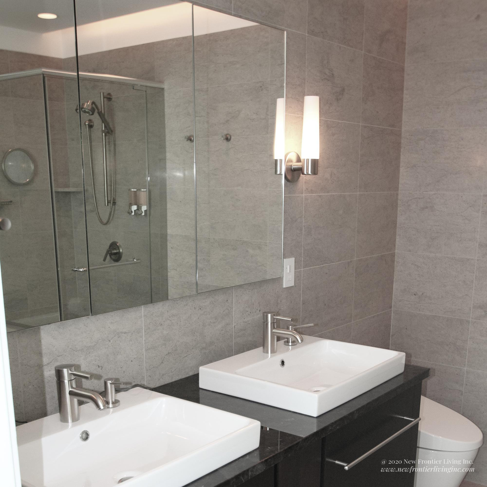 Cream brown bathroom installed by NFL Inc. two sinks and vanities and mirror