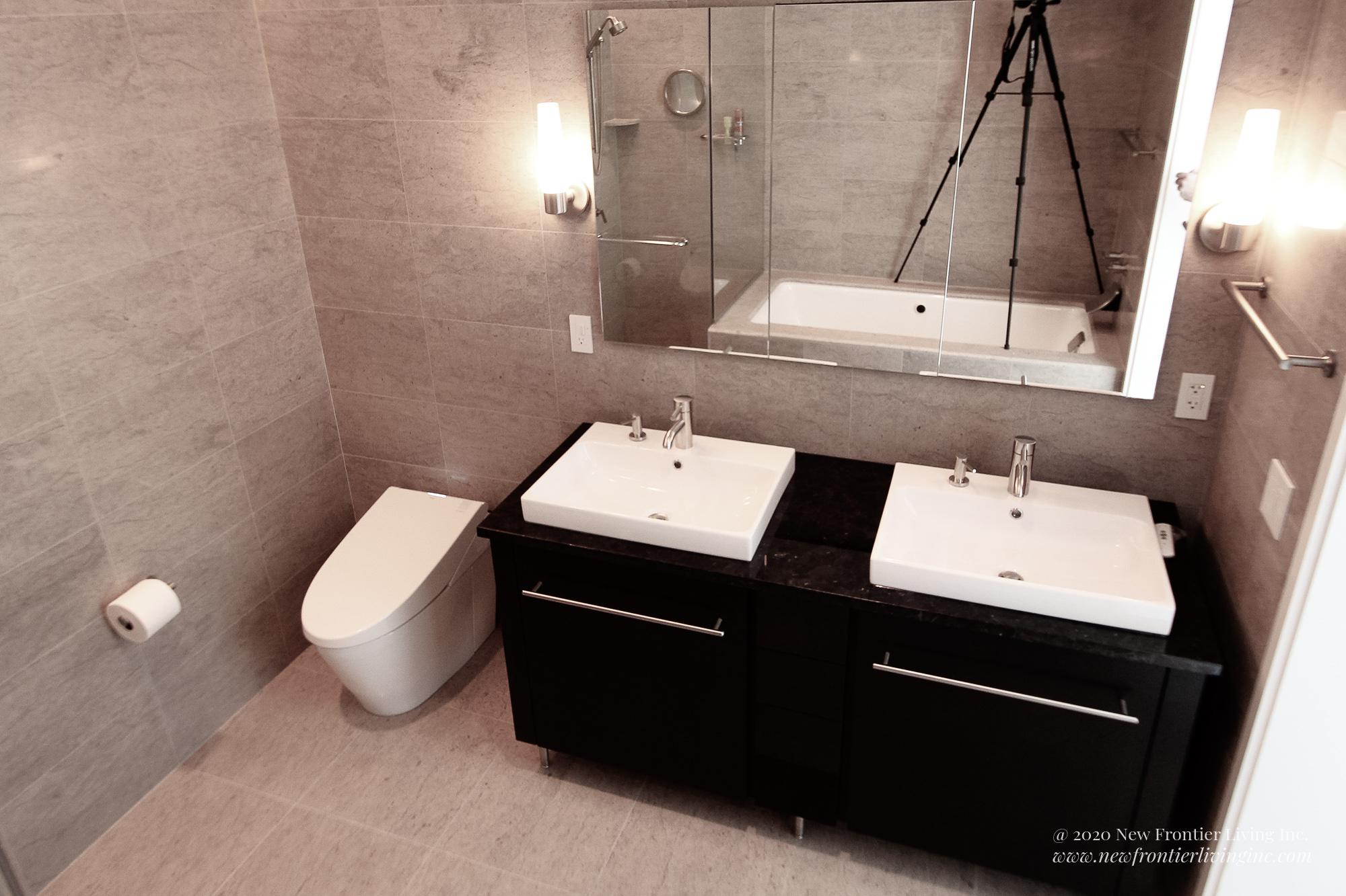 Cream brown bathroom installed by NFL Inc. two sinks and vanities and mirror and toilet on the left
