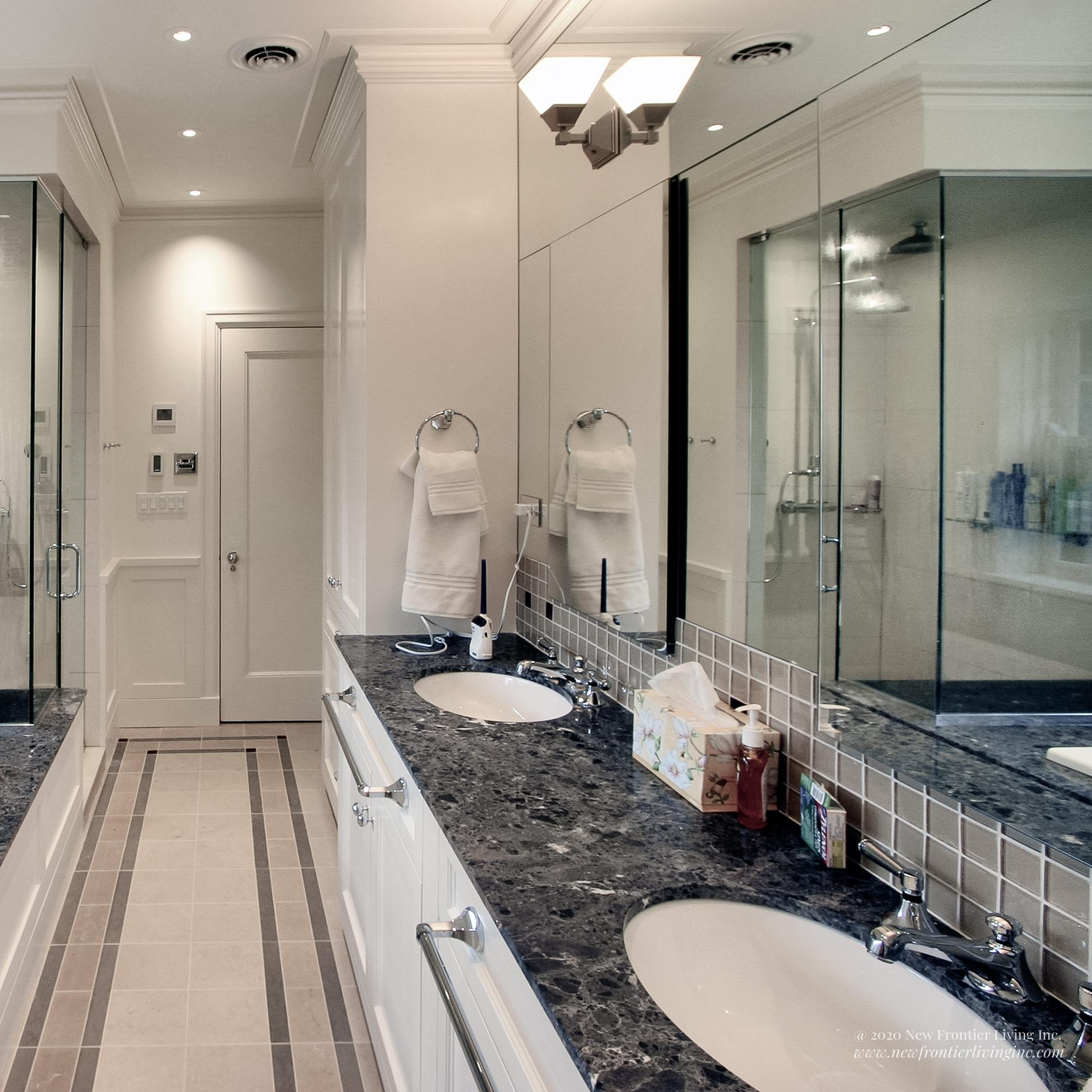 White bathroom with dark gray countertops, walk-in shower and double sink