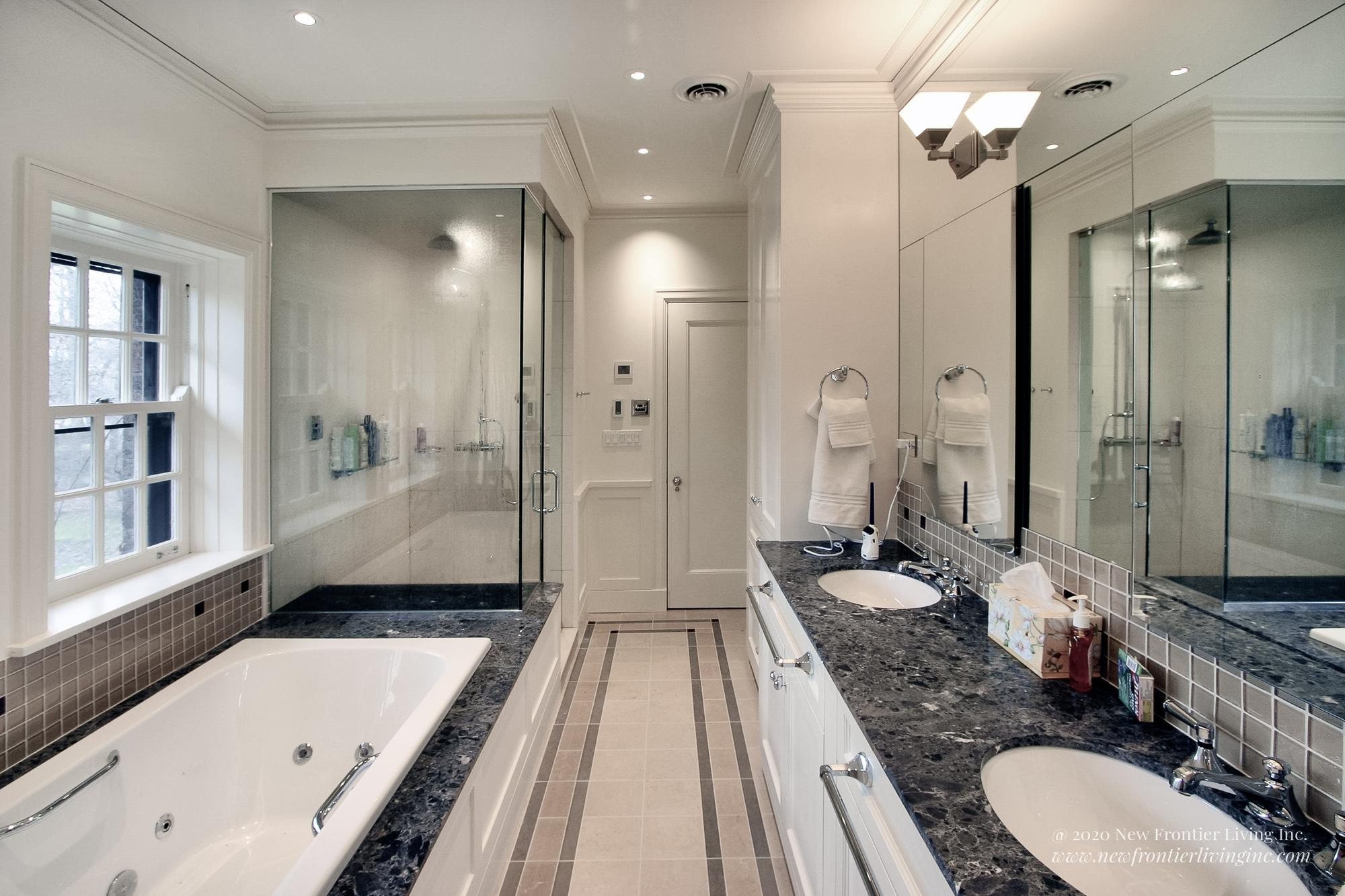 White bathroom with dark gray countertops, walk-in shower, tub on the left and double sink on the right