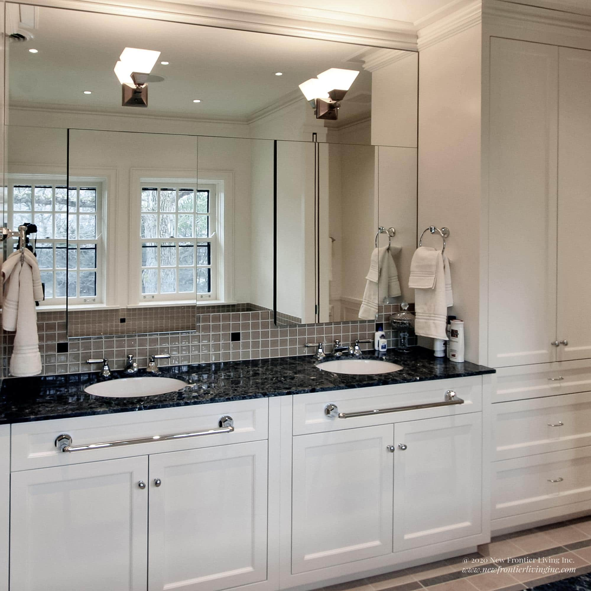 White bathroom with dark gray countertops and double sinks