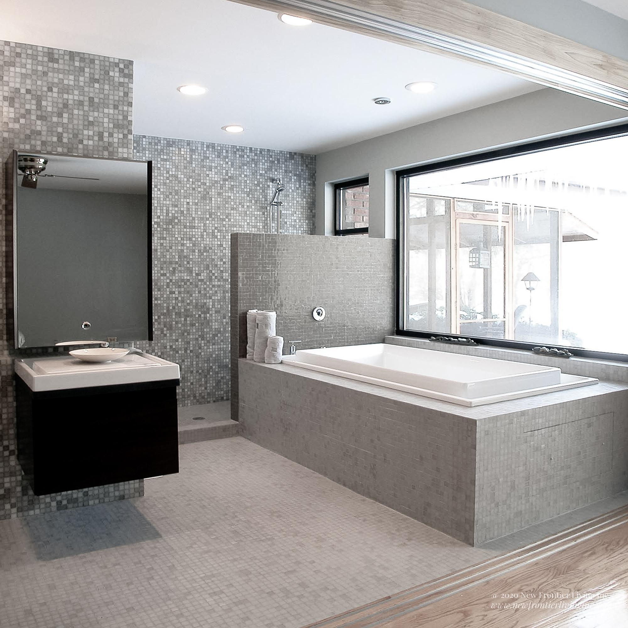 White and gray all ceramic bathroom with a tub and sink and