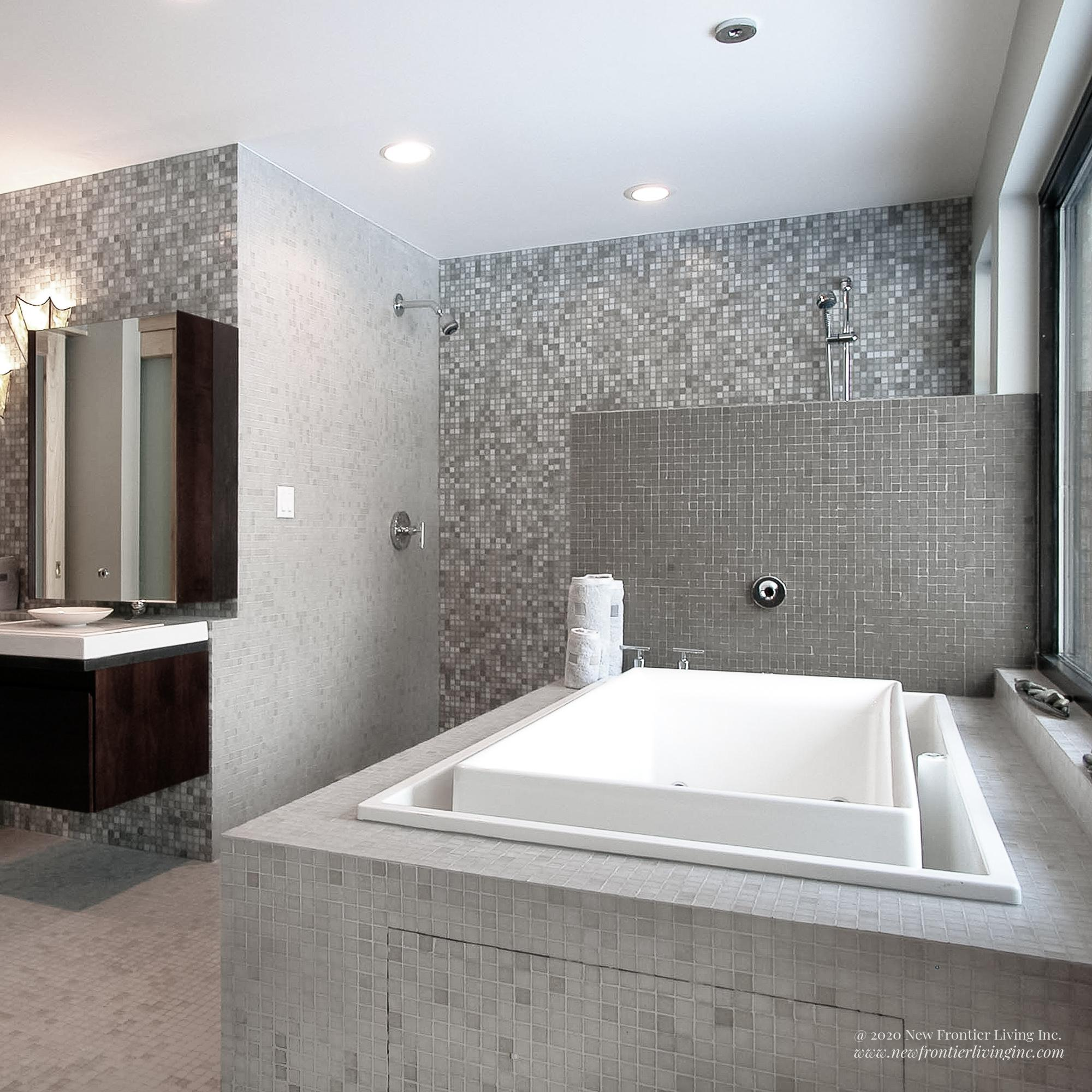 White and gray all ceramic bathroom with a tub and sink and standup-shower without a door