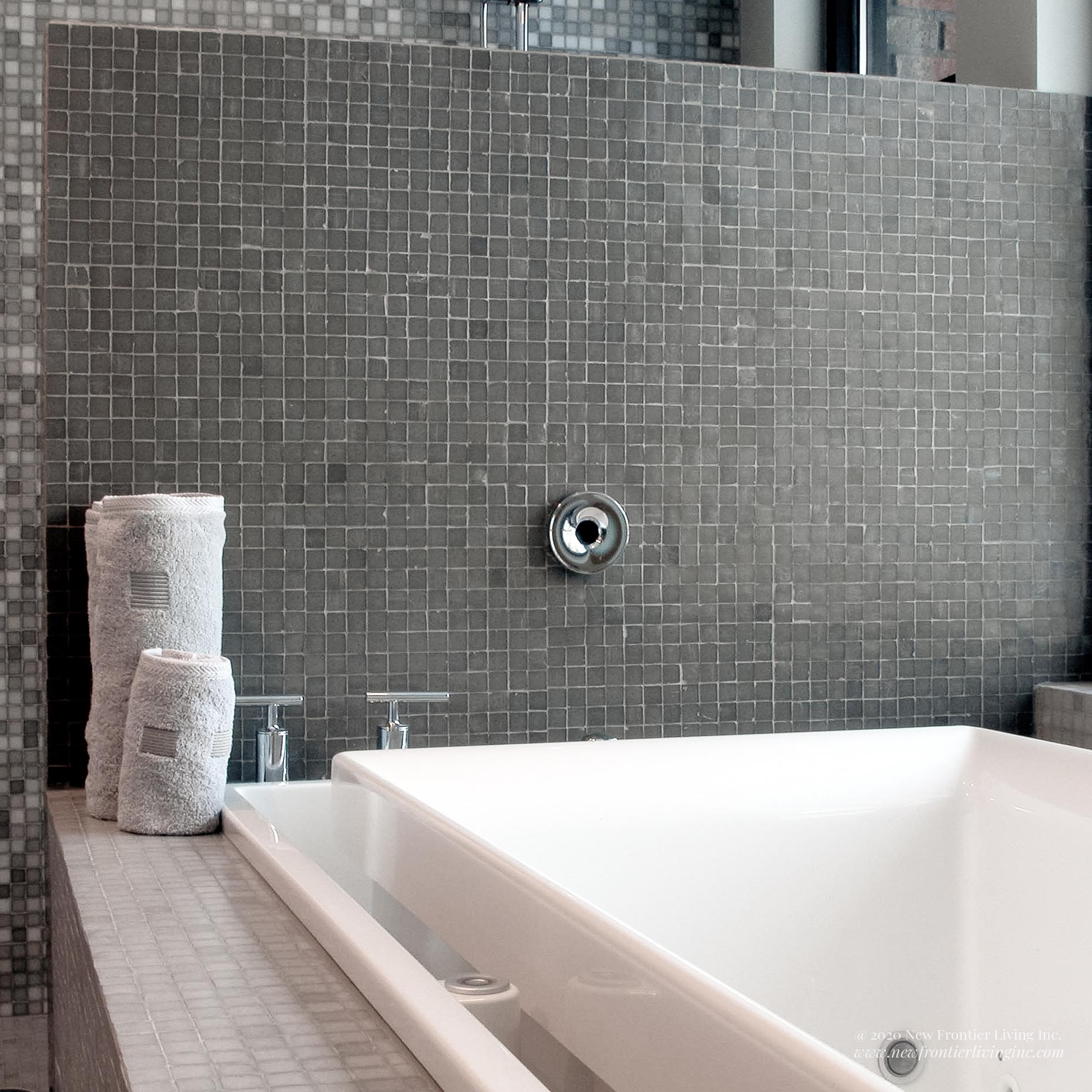 Close-up of ceramic tiles on the bathtub splash and two towels