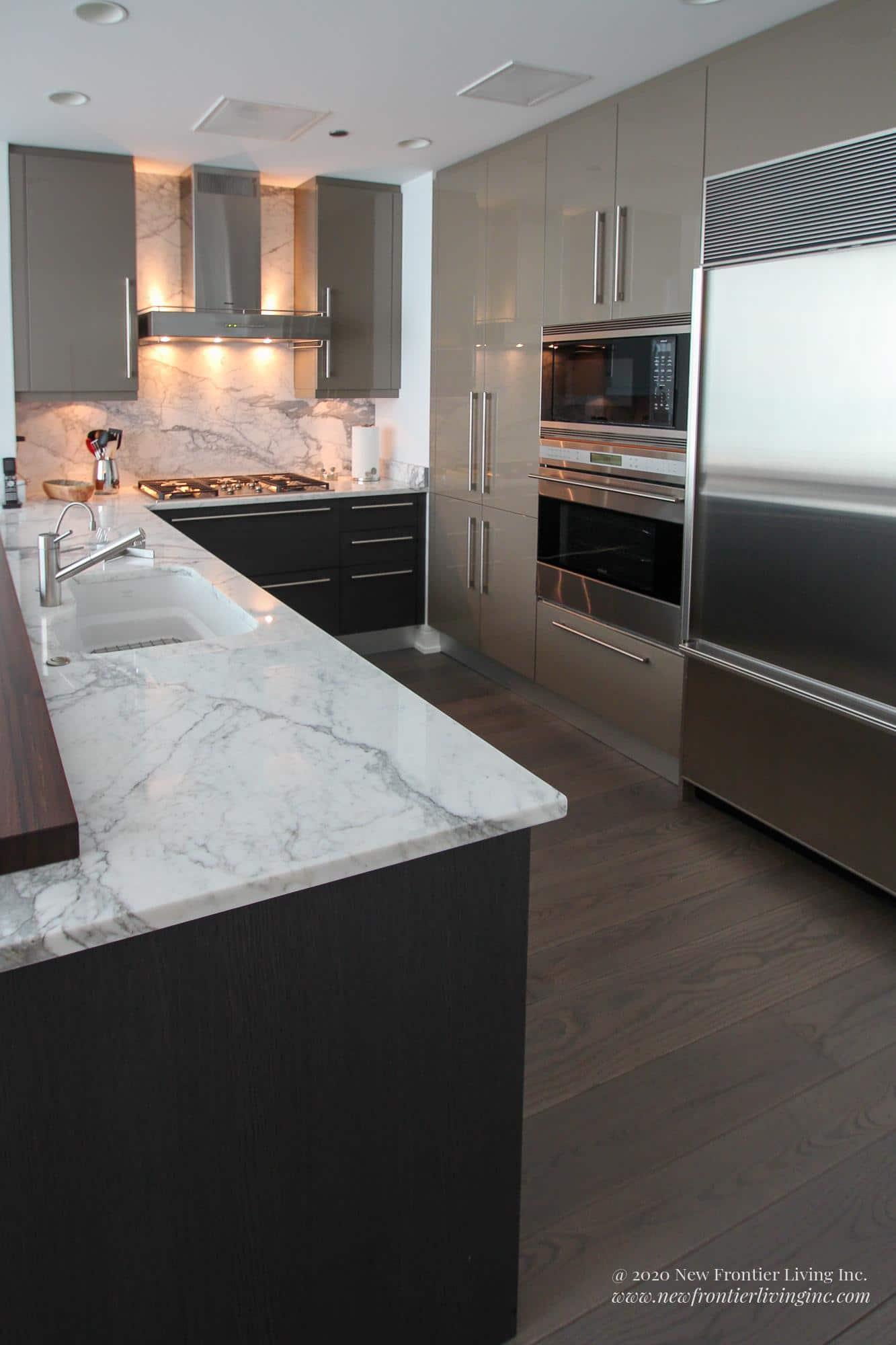 Dark gray kitchen with white granite countertop, dark floors and sink on the island