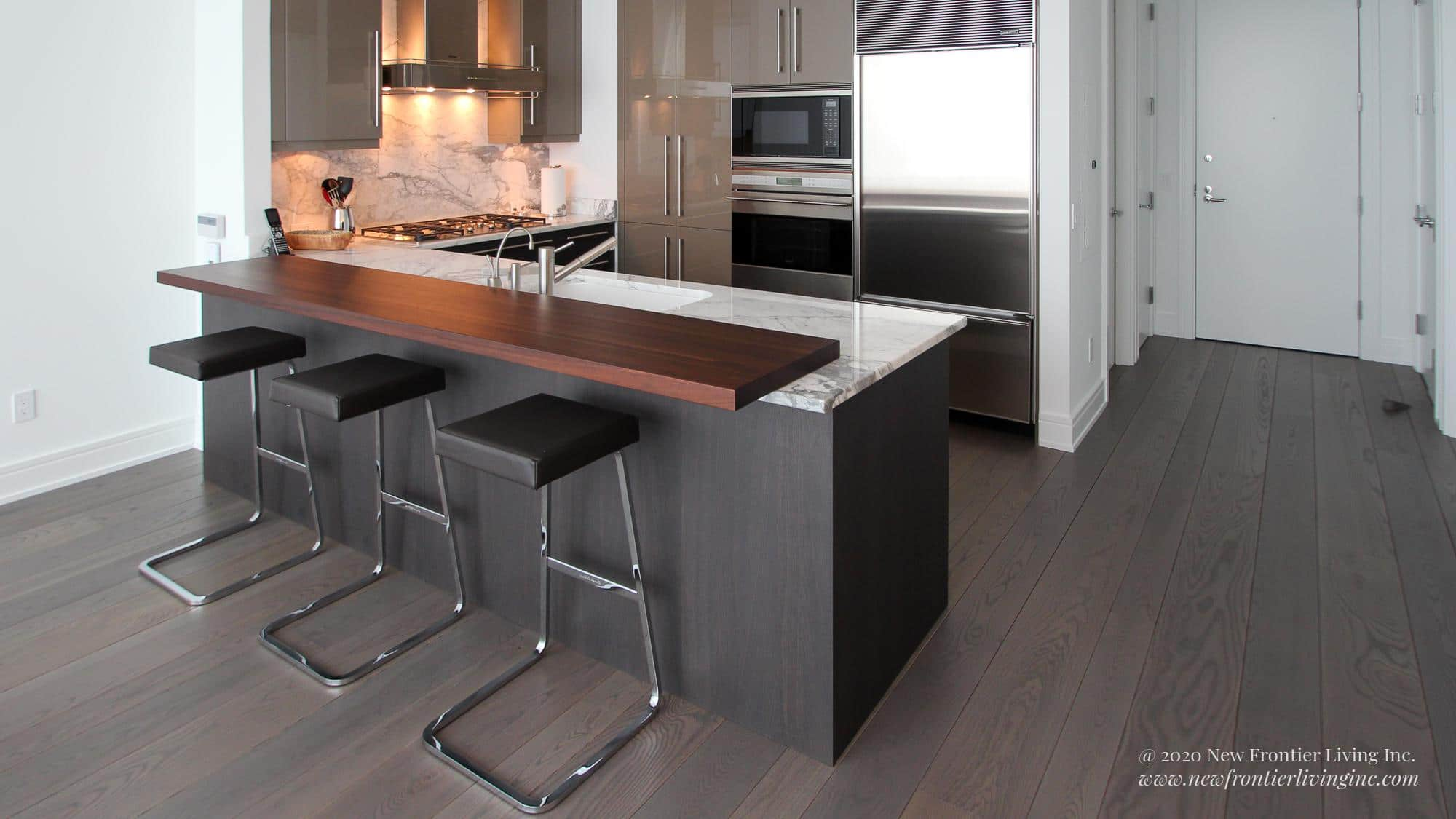 Dark gray kitchen with white granite countertop and brown ledge, long view of entire kitchen