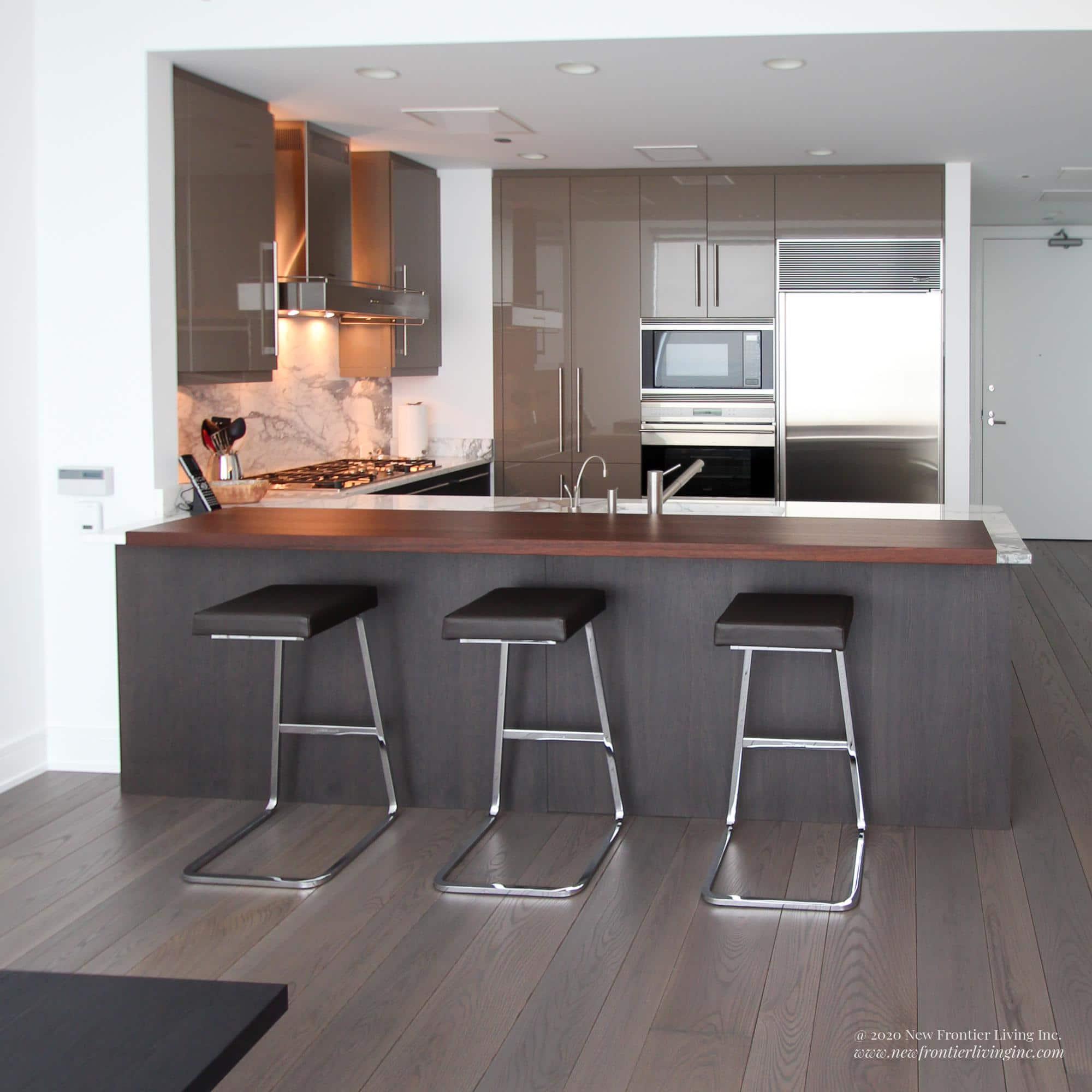 Dark gray kitchen island with white granite counter and three stools