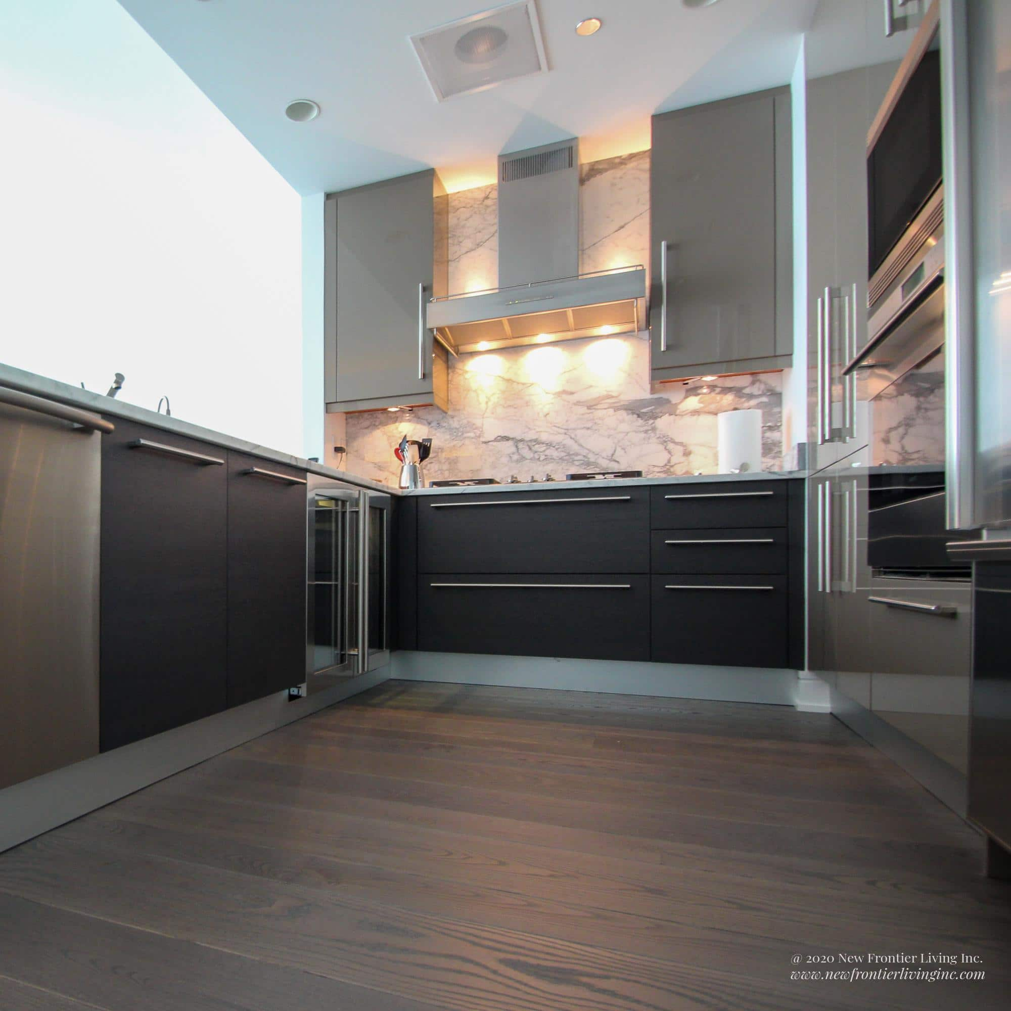 Dark gray kitchen cabinets and dark gray wooden floor, long hood, low angle view
