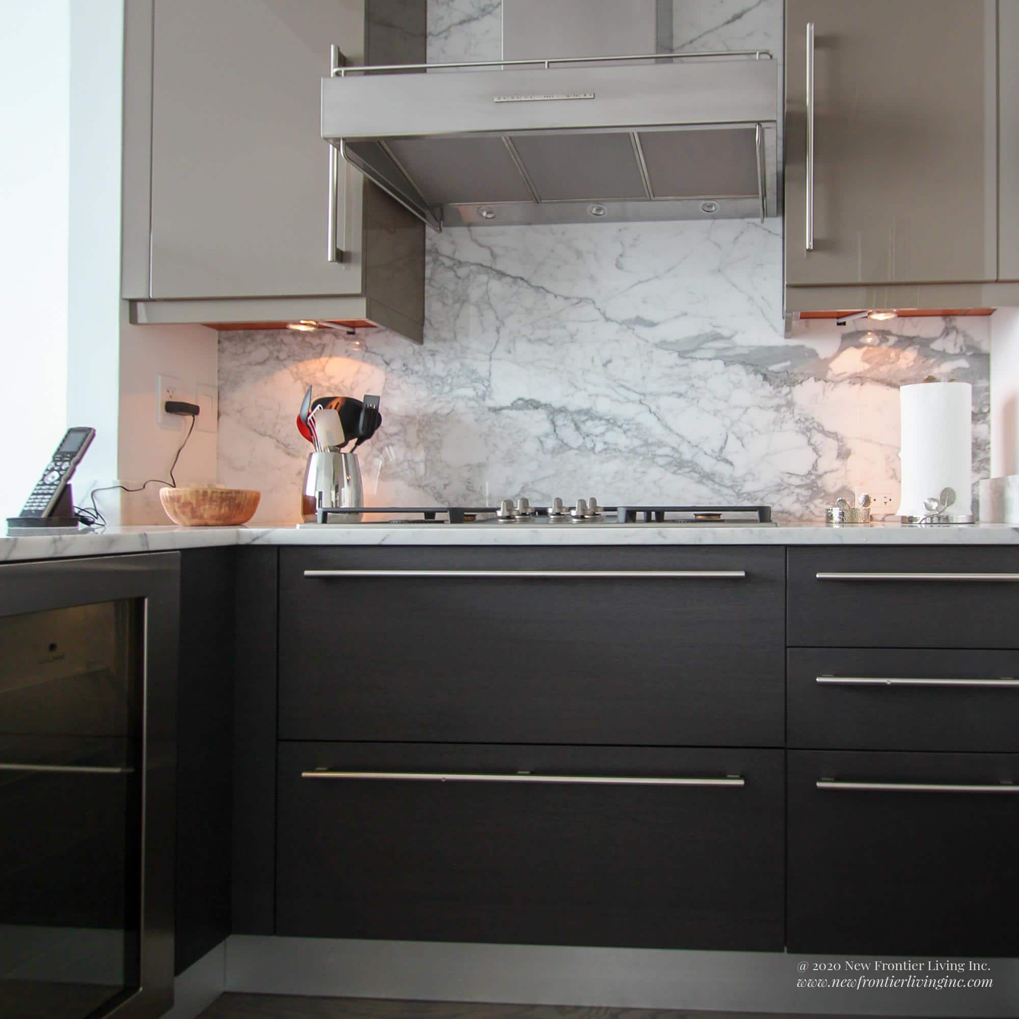 Dark gray kitchen bottom cabinets with silver handles cooktop view
