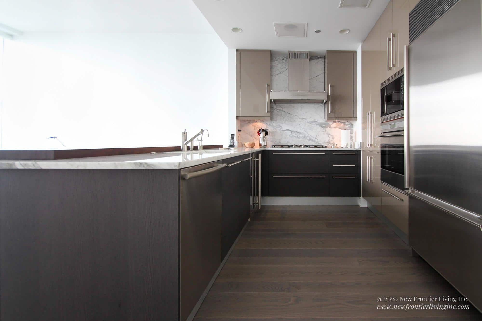 Dark gray kitchen cabinets and dark gray wooden floor, sink and counter on the left, cooktop front, oven and fridge on the right