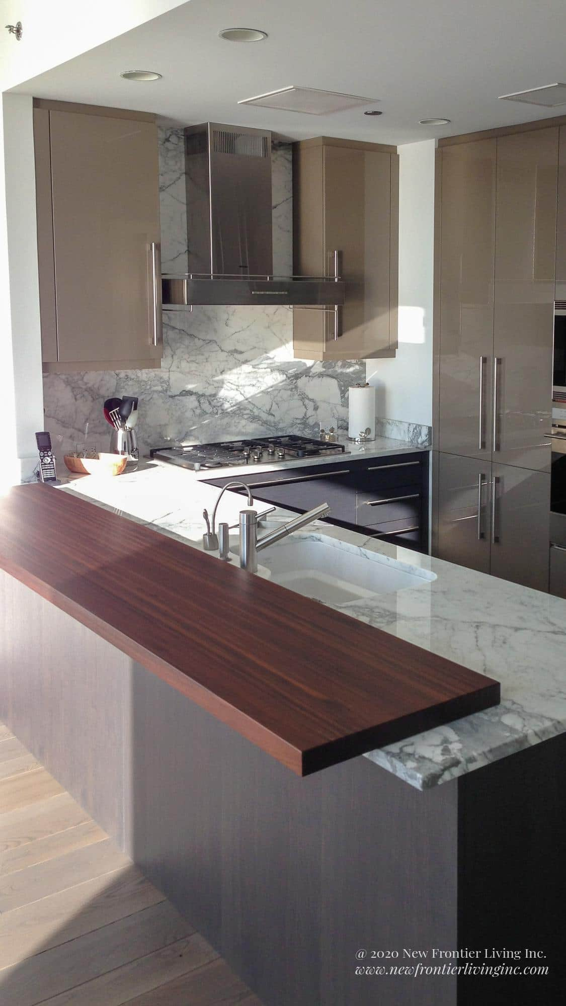 Dark gray kitchen island with white granite counter and extended brown ledge close-up