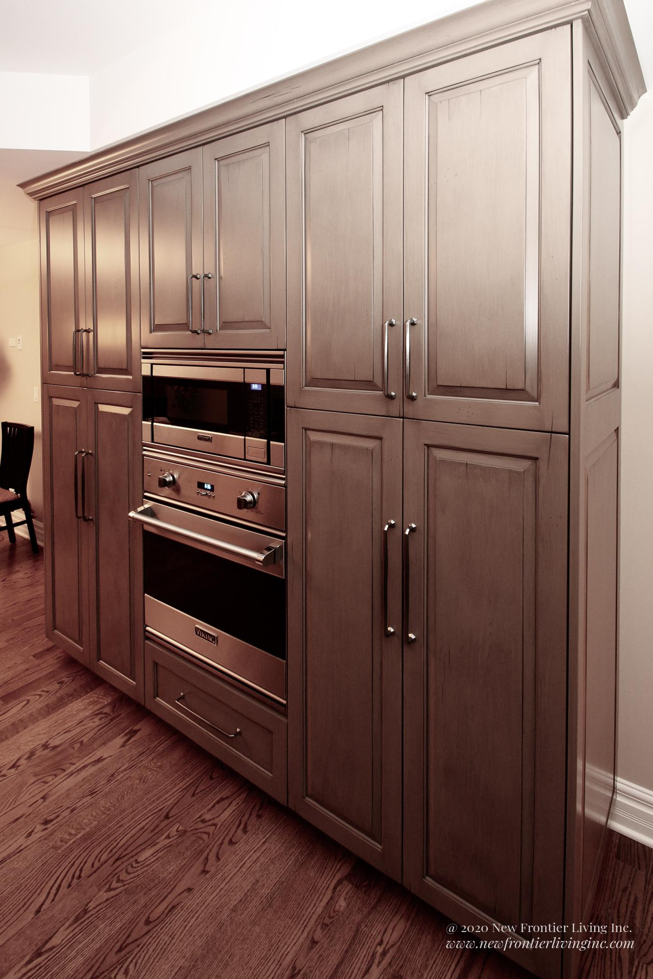Custom light brown kitchen large storage cabinets and microwave and oven