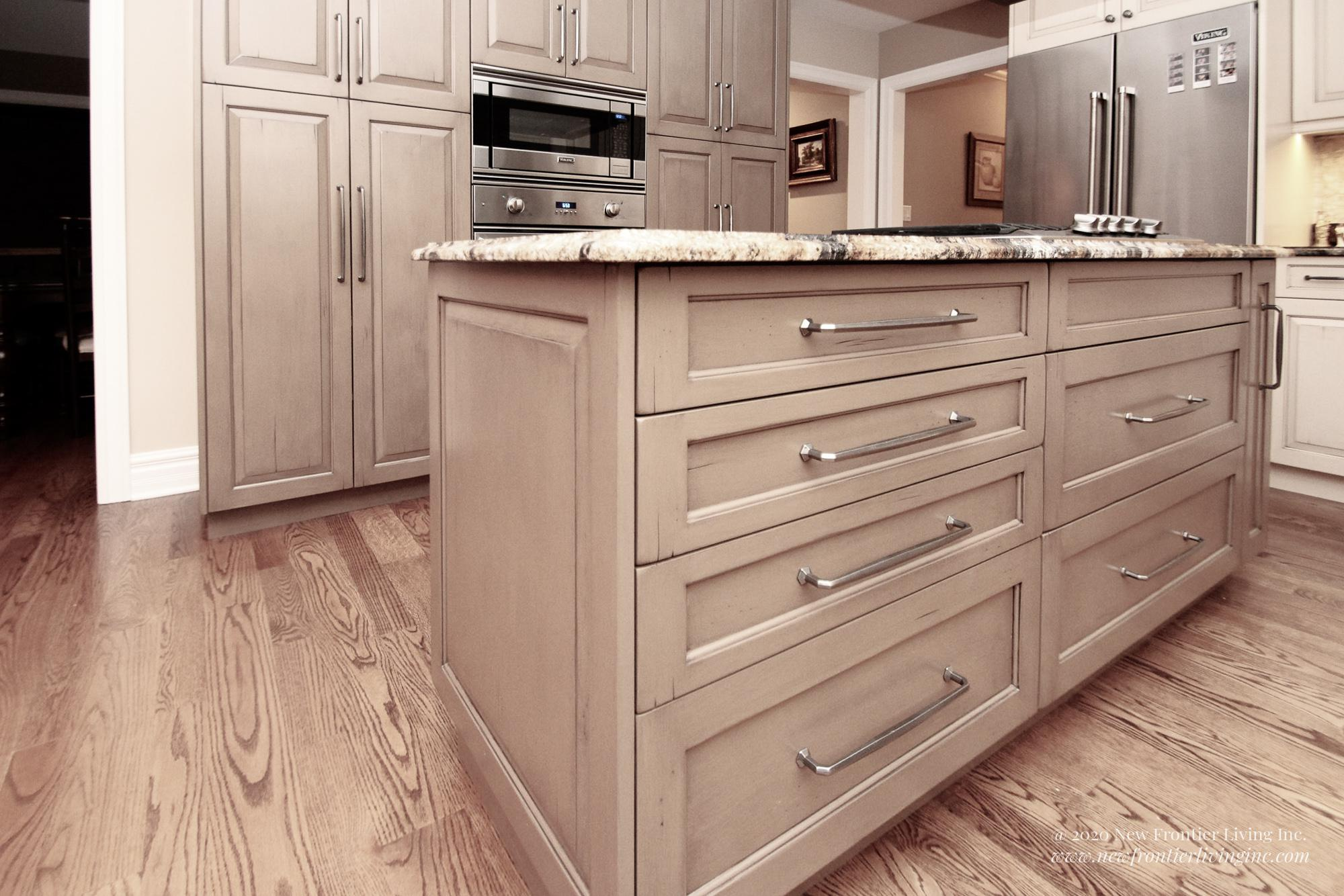 Custom light brown kitchen with island and cabinets, oven and fridge in the back close-up
