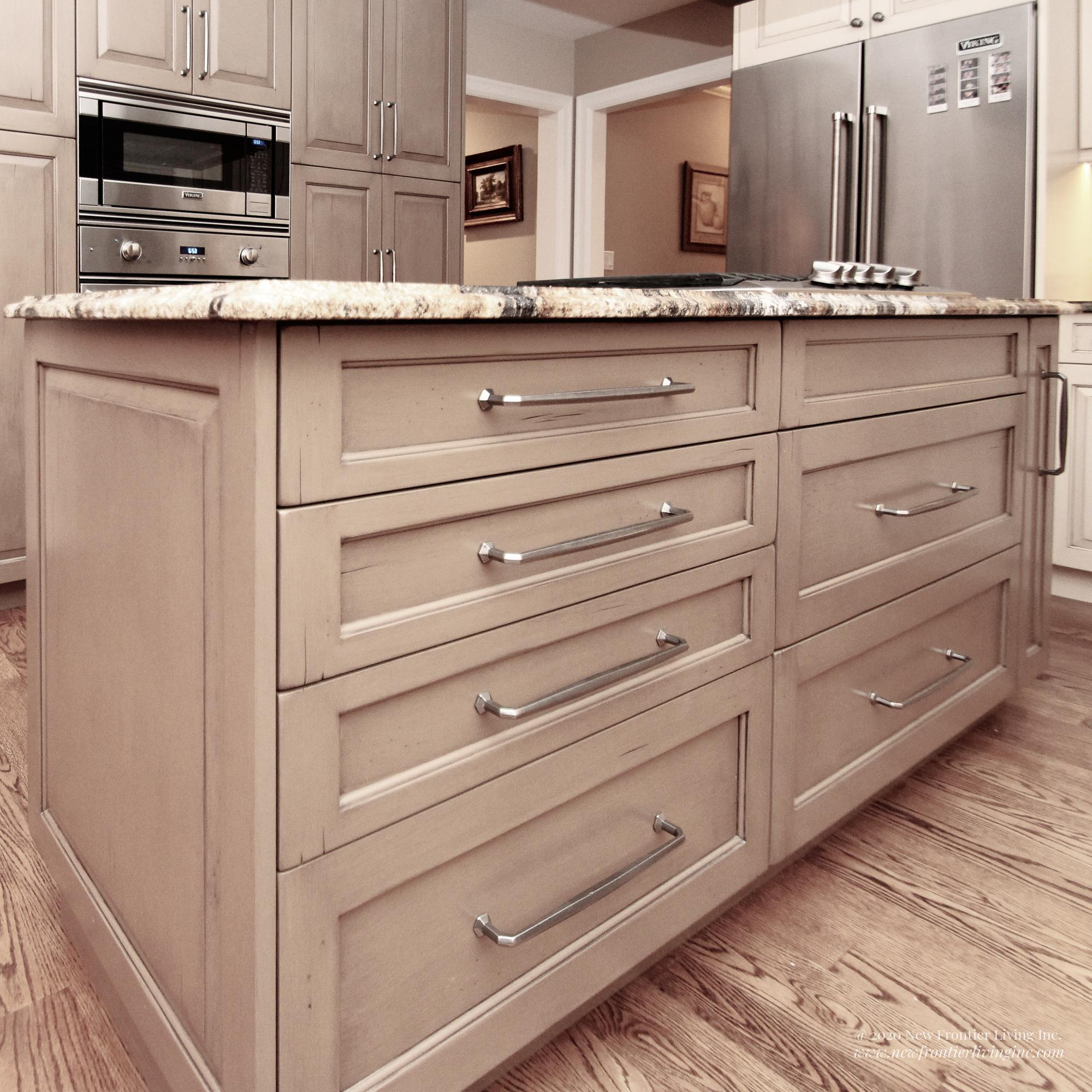 Custom light brown kitchen with island and cabinets, oven and fridge in the back