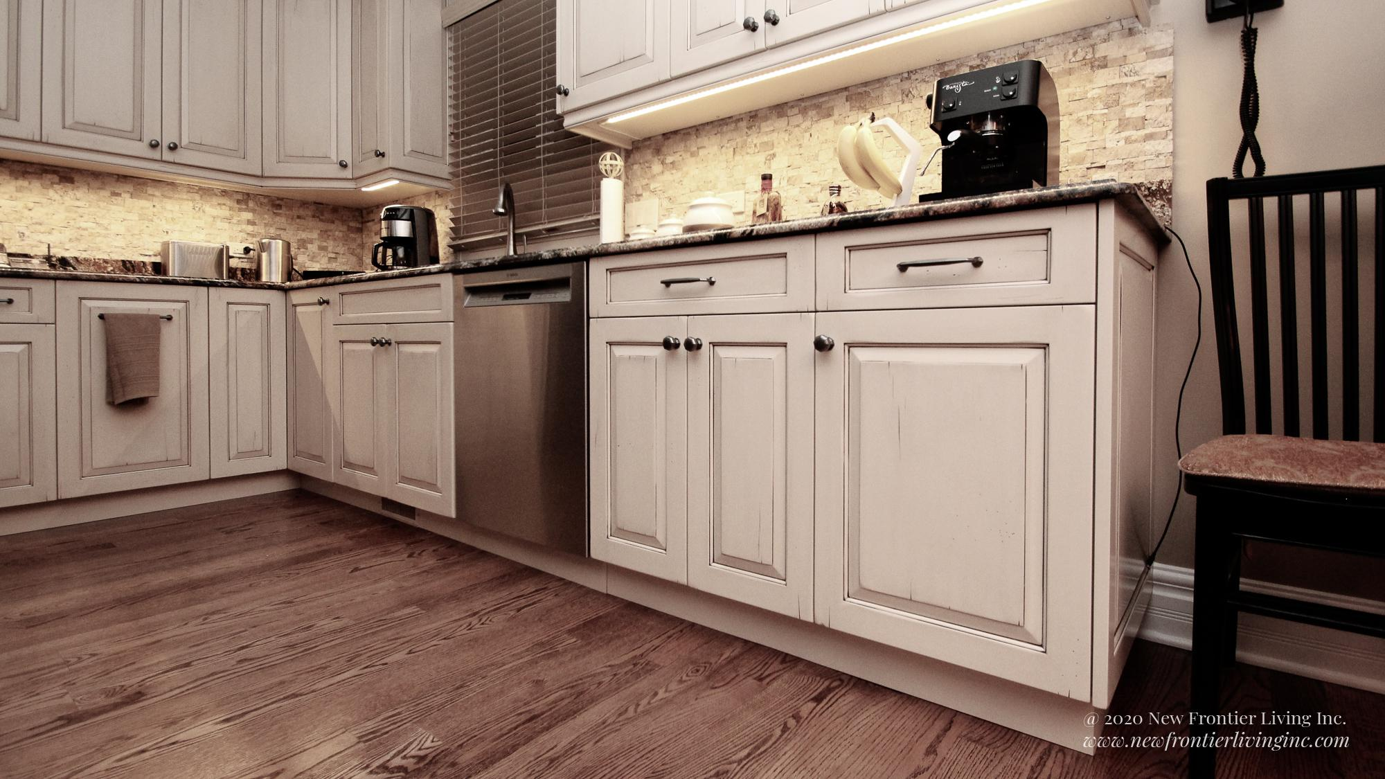 Custom light brown kitchen lower cabinets, dishwasher and small appliances on the countertop