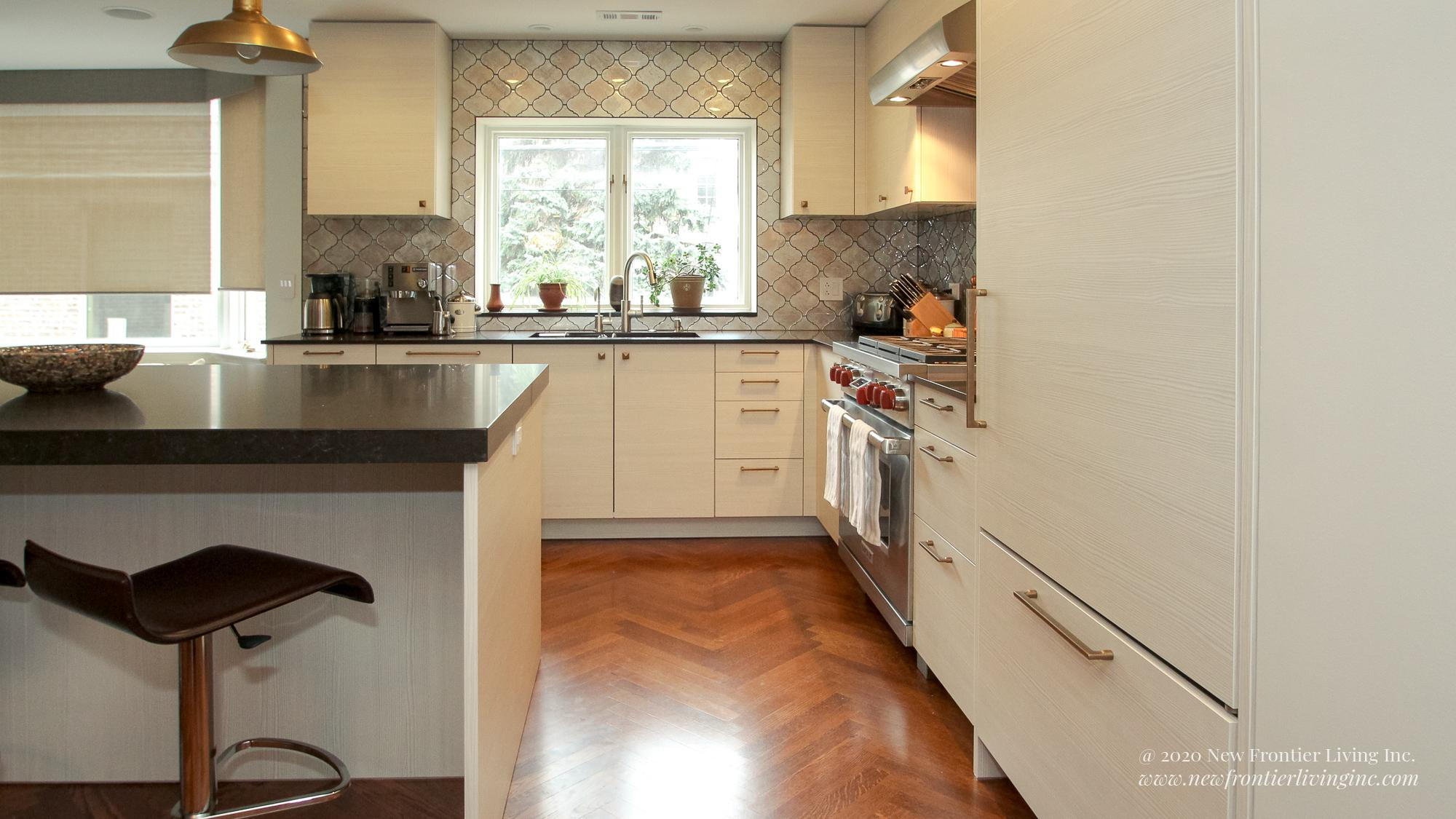 Cream kitchen bottom cabinets and wooden floor flowers in the kitchen windows and small appliances on the counter