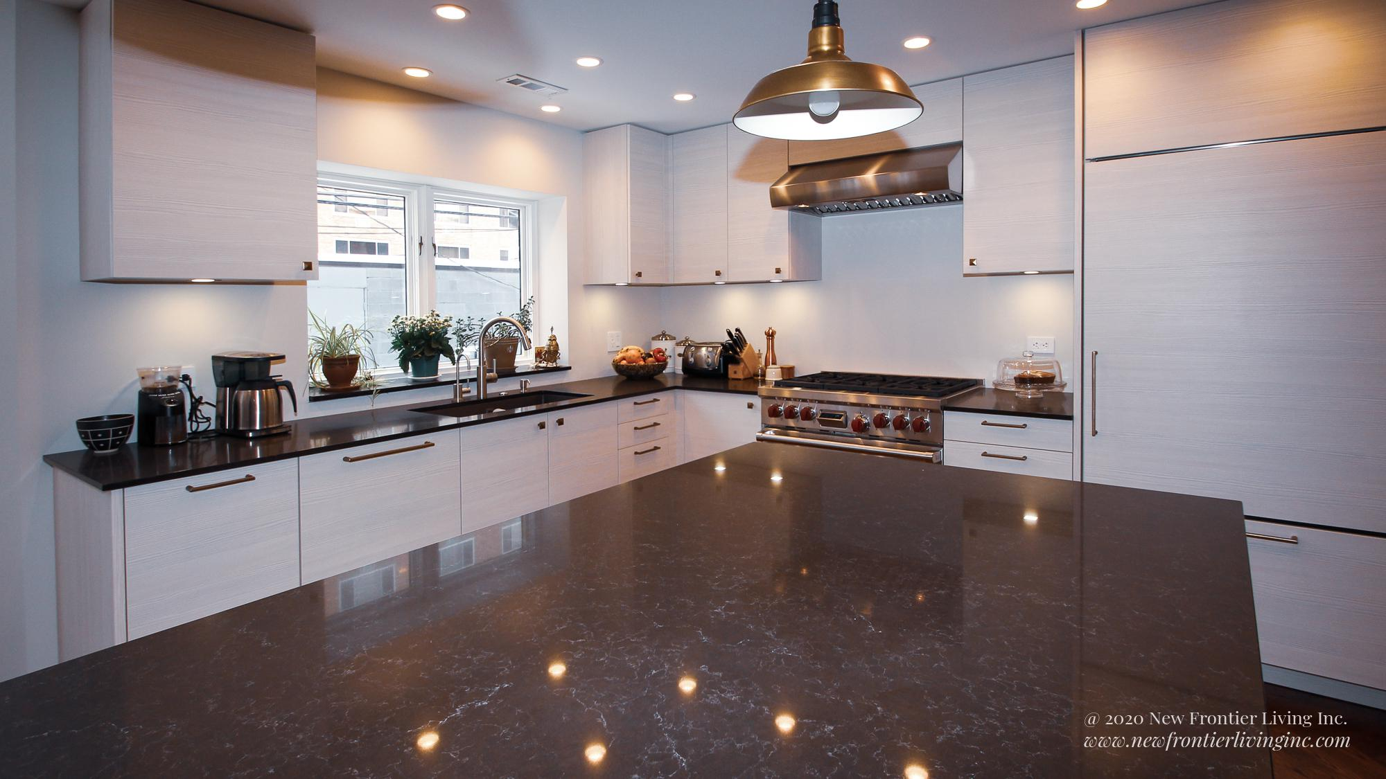 Cream kitchen with black countertop island view on to the other side with kitchen sink and cooktop