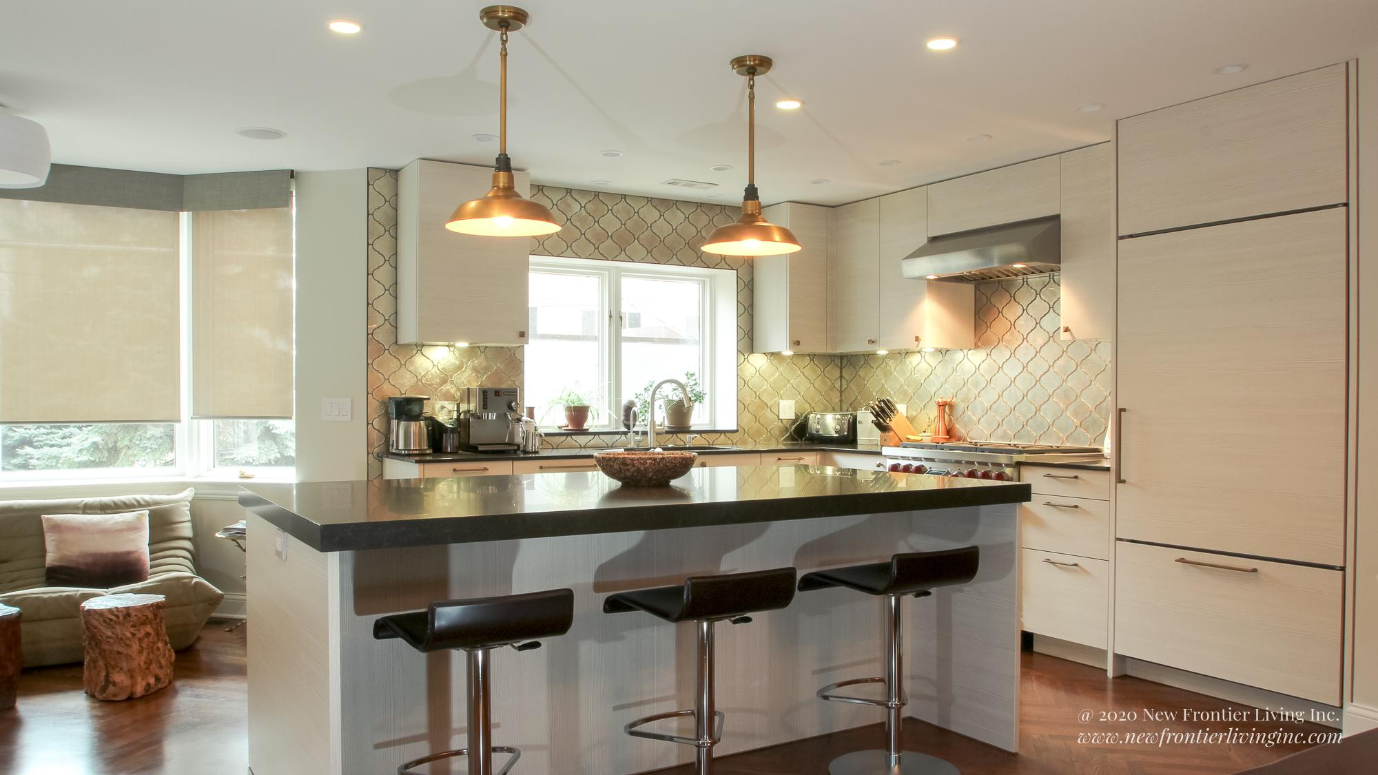 Cream kitchen with black countertops with an island, view toward windows, long pendant lighting and bar stools