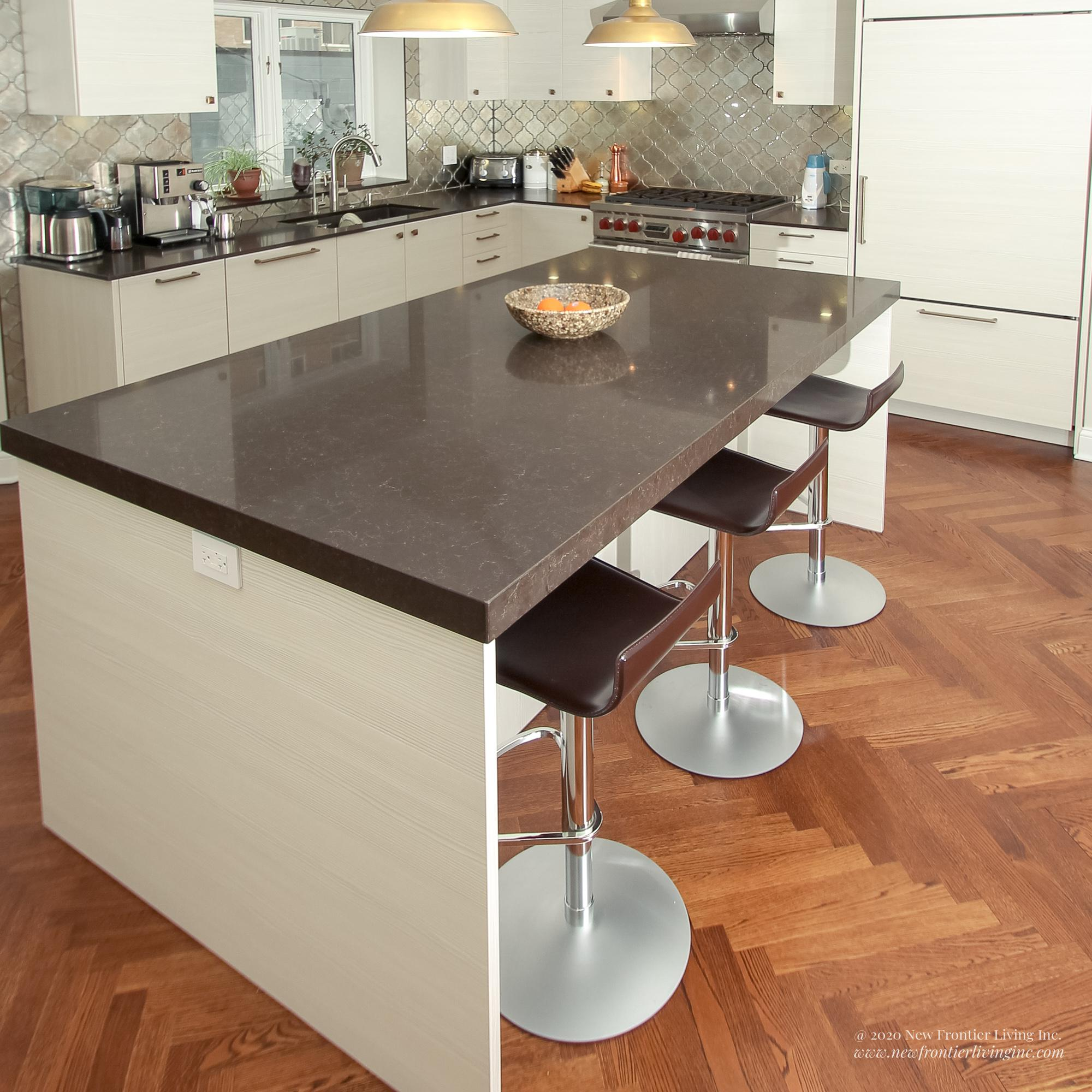 Cream kitchen with black countertops with an island and three bar stools close-up