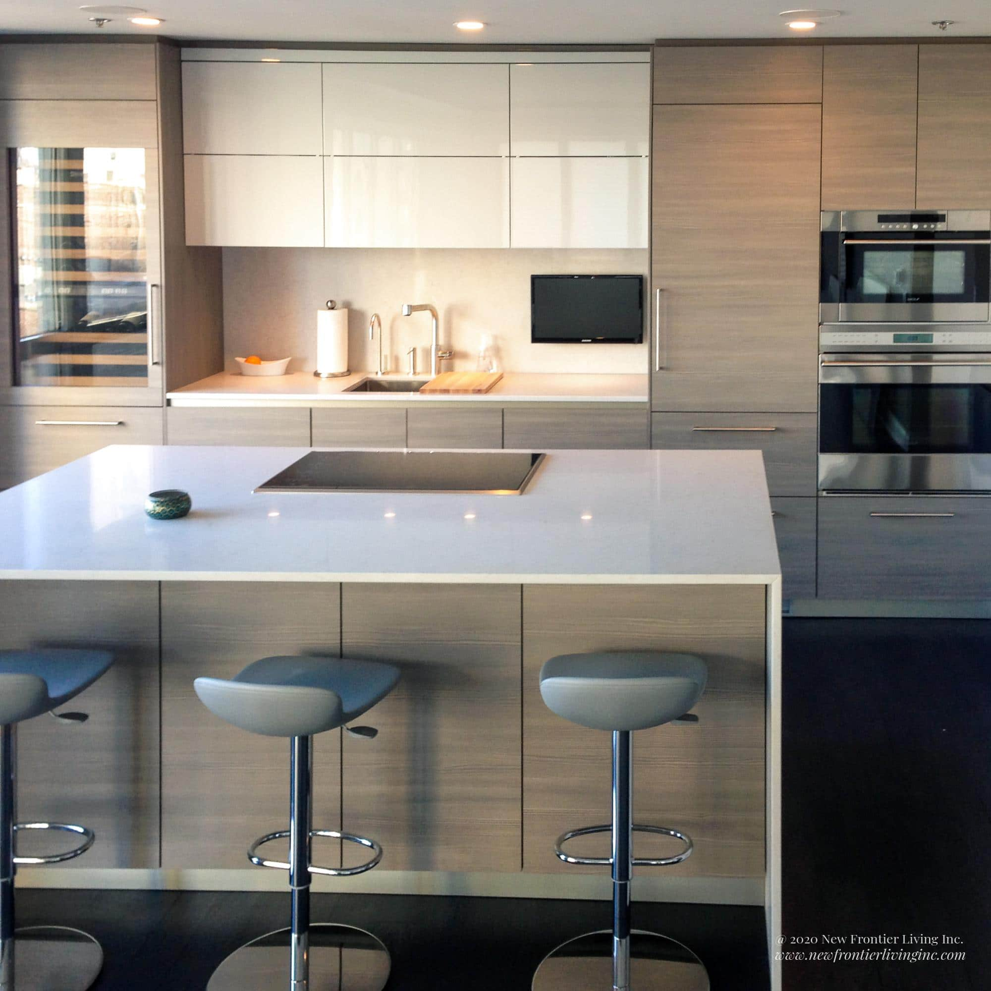 Light wood kitchen with a waterfall island and white countertop and three bar stools