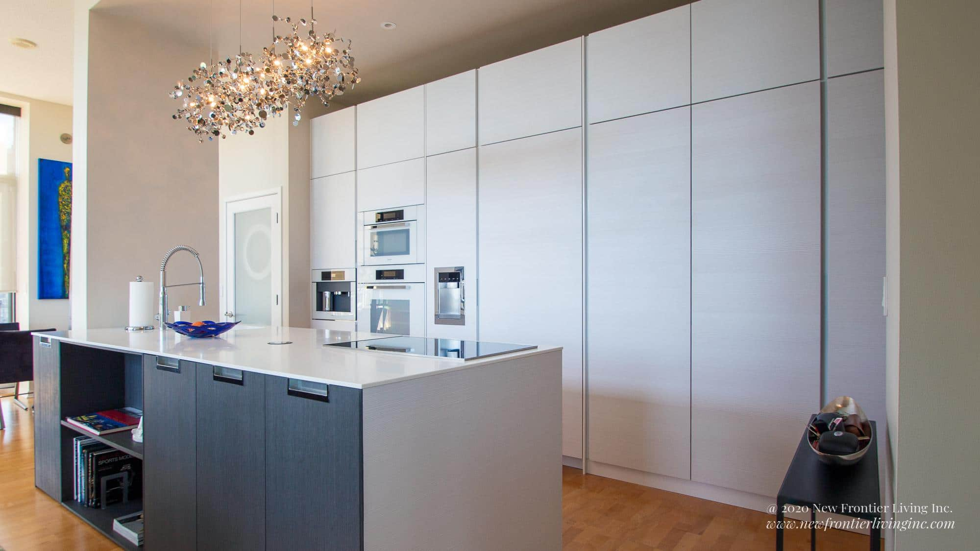 White waterfall kitchen island with black cabinetry, hanging pendant lights above