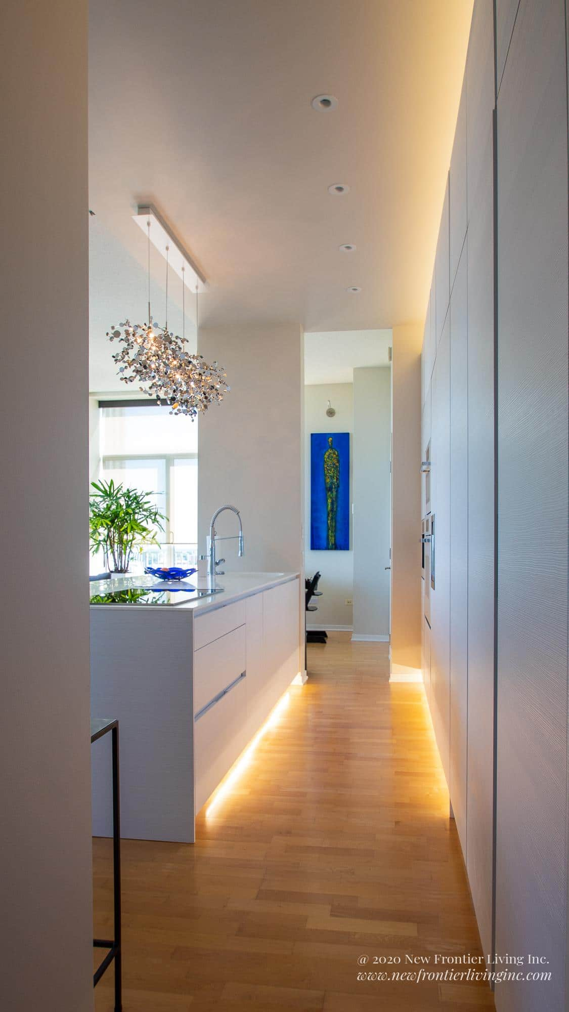 White kitchen waterfall island with LED lights underneath the cabinets and on the right white wall cabinetry with LED lights underneath