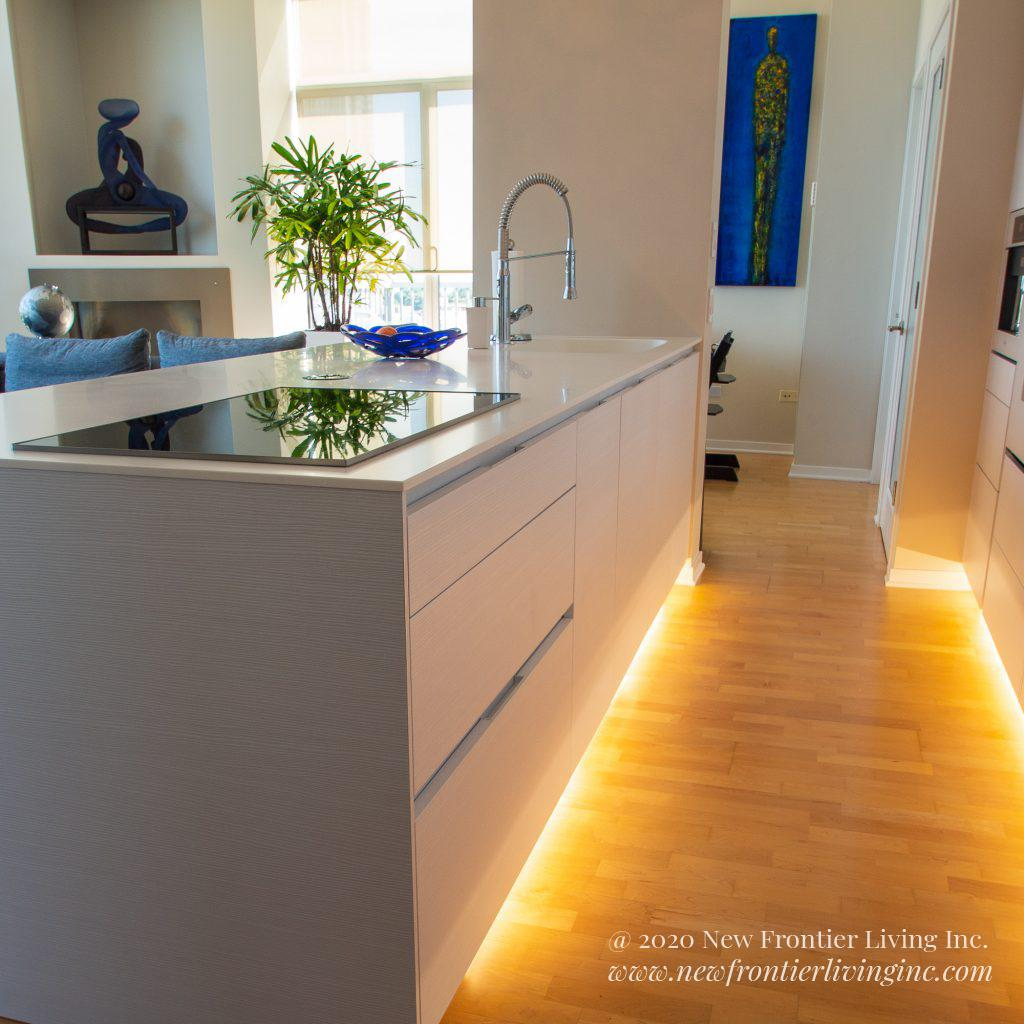 White kitchen waterfall island with LED lights underneath the cabinets