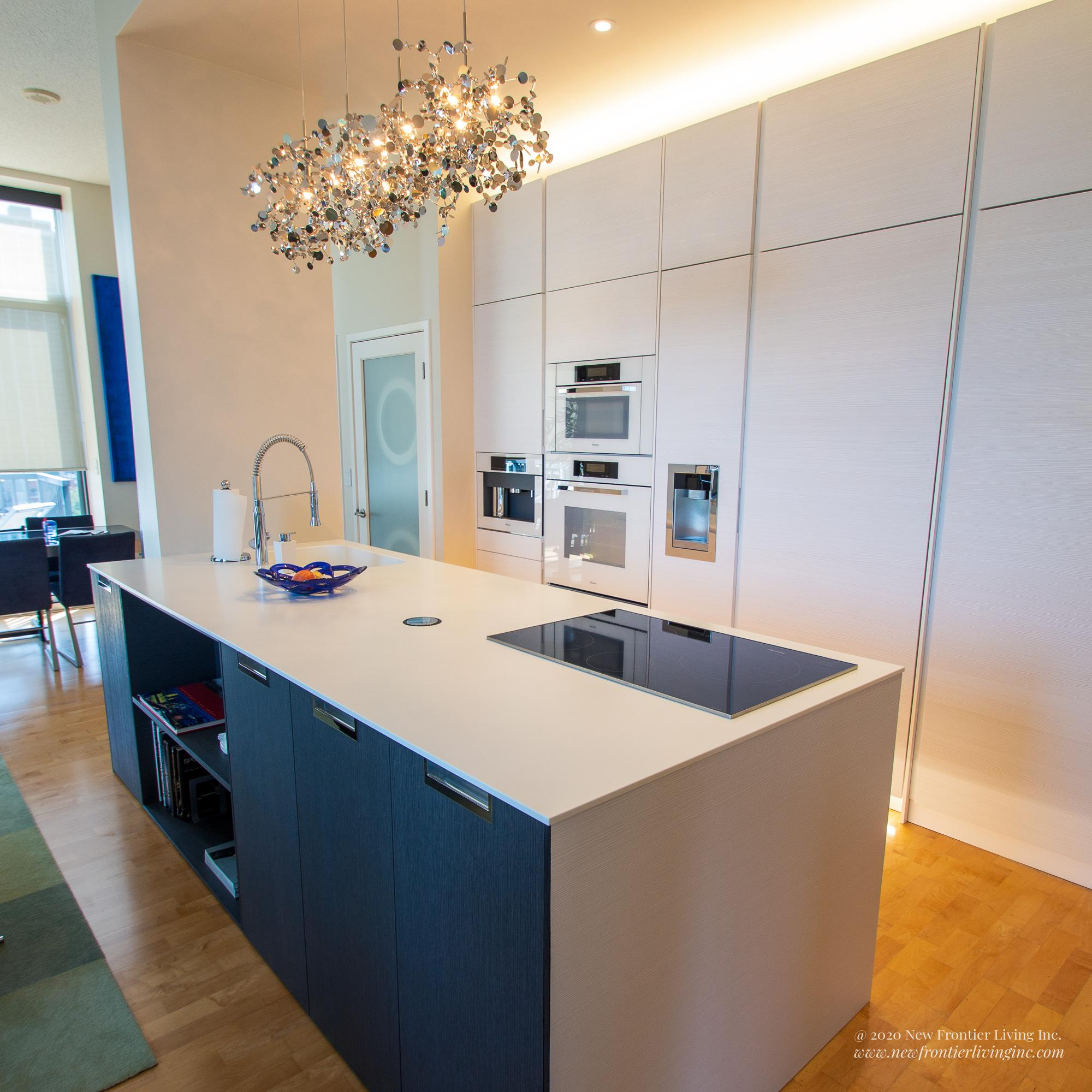 White waterfall kitchen island with black cabinetry and induction cooktop, large white cabinetry on the wall with appliances