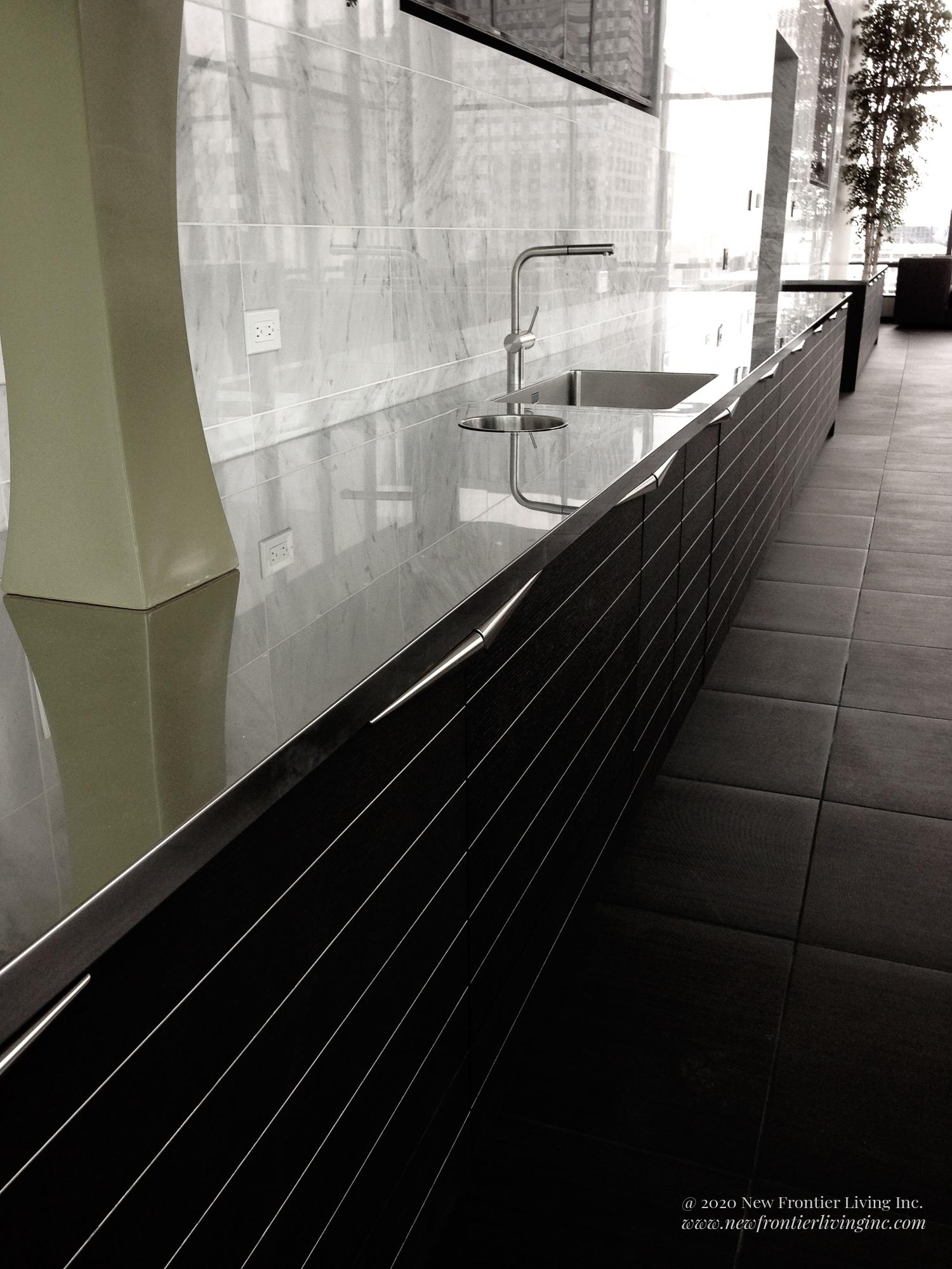 Long row of black cabinetry by the wall, with a sink and faucet, large backsplash