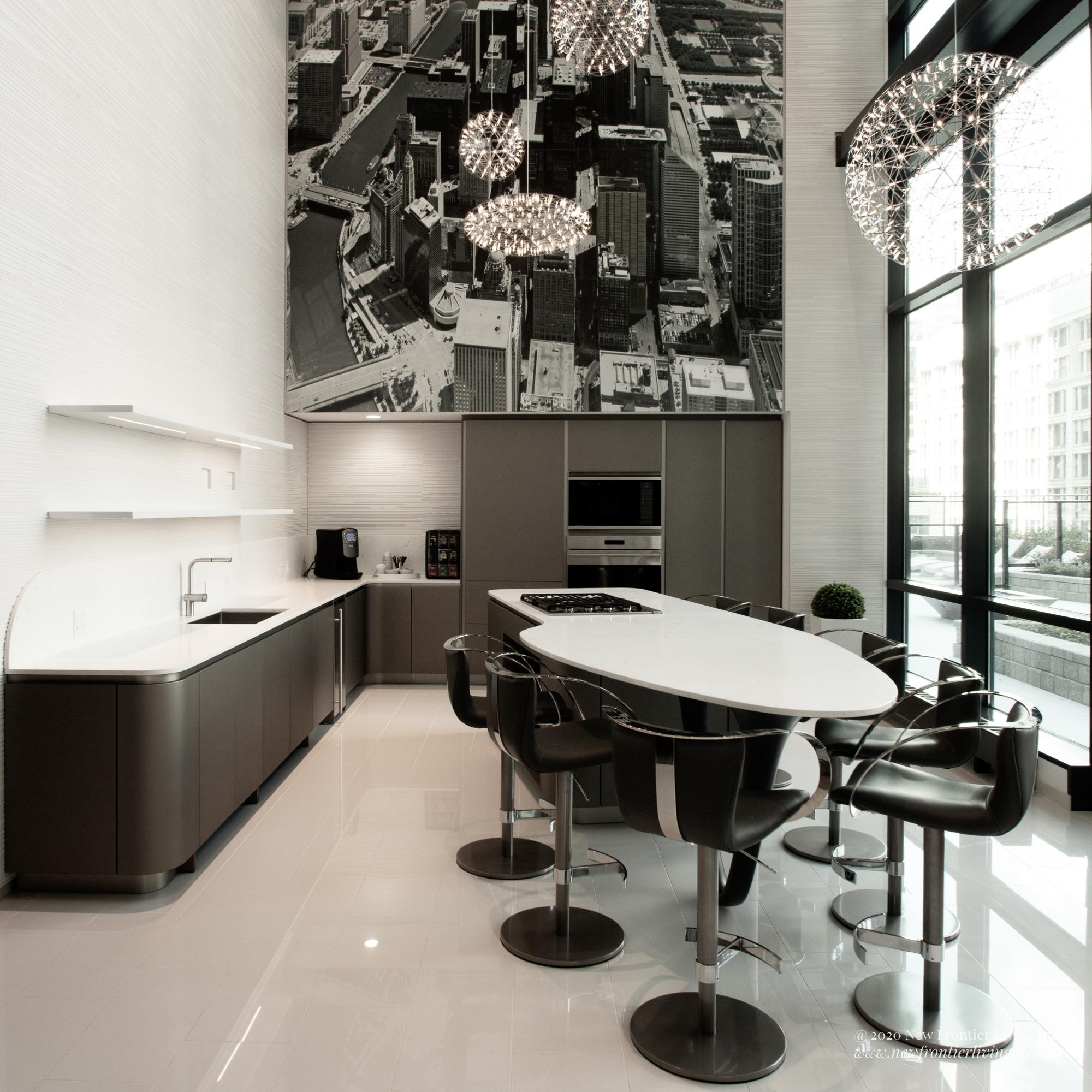 Large view of a black kitchen with white countertops and island, hight ceiling, large view of the city painting overhead, many bar stools by the island