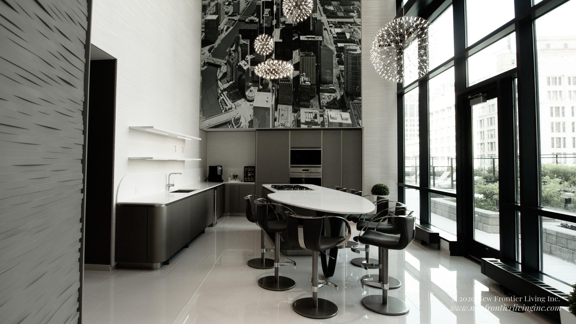 Large view of a black kitchen with white countertops and island, hight ceiling, patio on the roof on the right