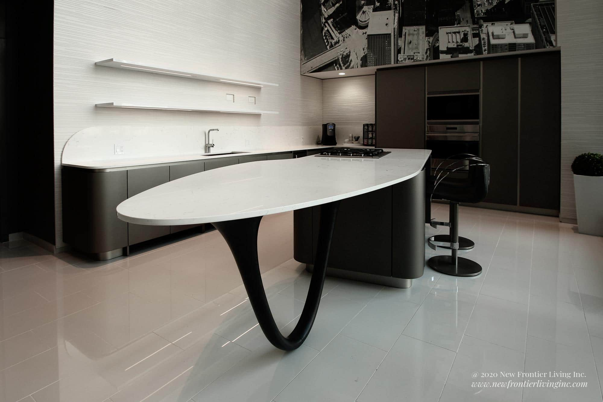 Black kitchen with white countertops and island, island in the shape of a spaceship