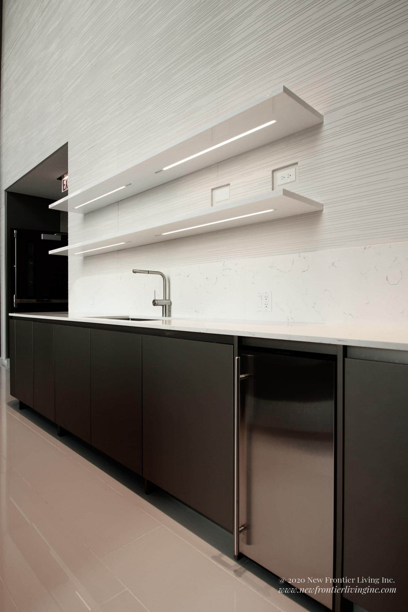 Black bottom cabinetry with white countertop, sink and dishwasher, two white shelves above