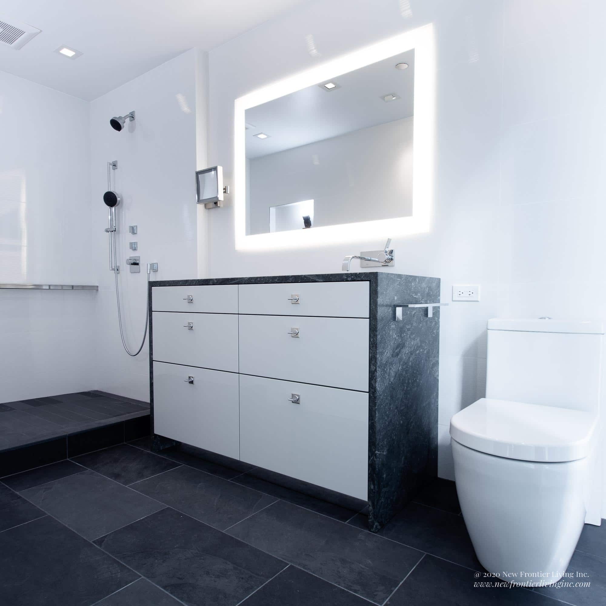 White and gray bathroom with walk-in shower, sink and vanity and LED lighted mirror in the middle and toilet on the right