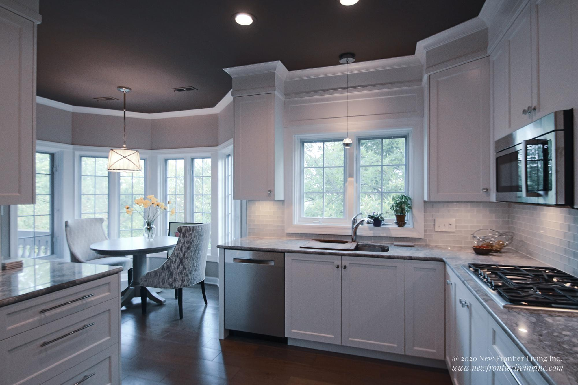 White kitchen with a dinning nook and windows