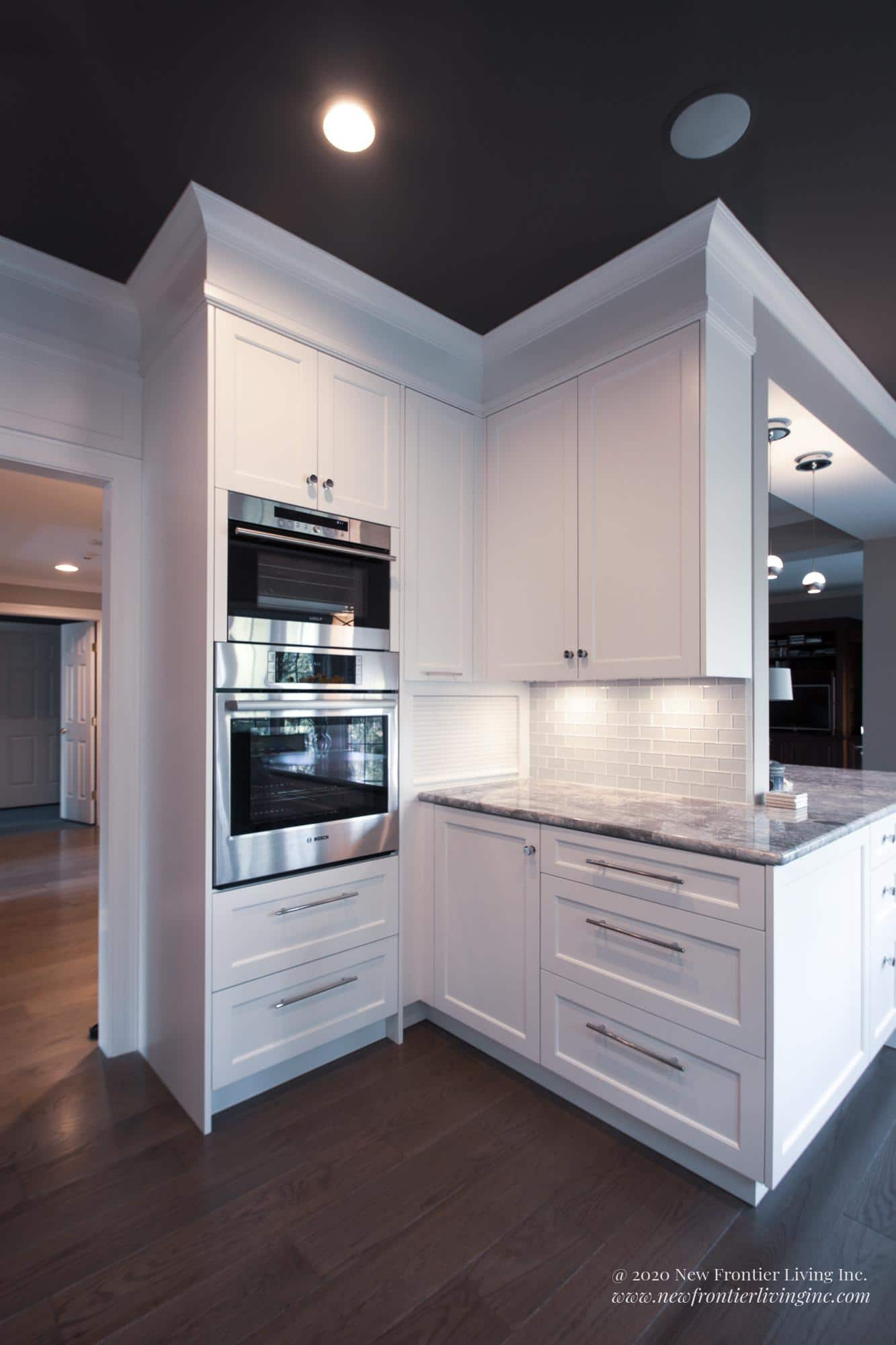 White kitchen cabinetry on the corner with oven and microwave