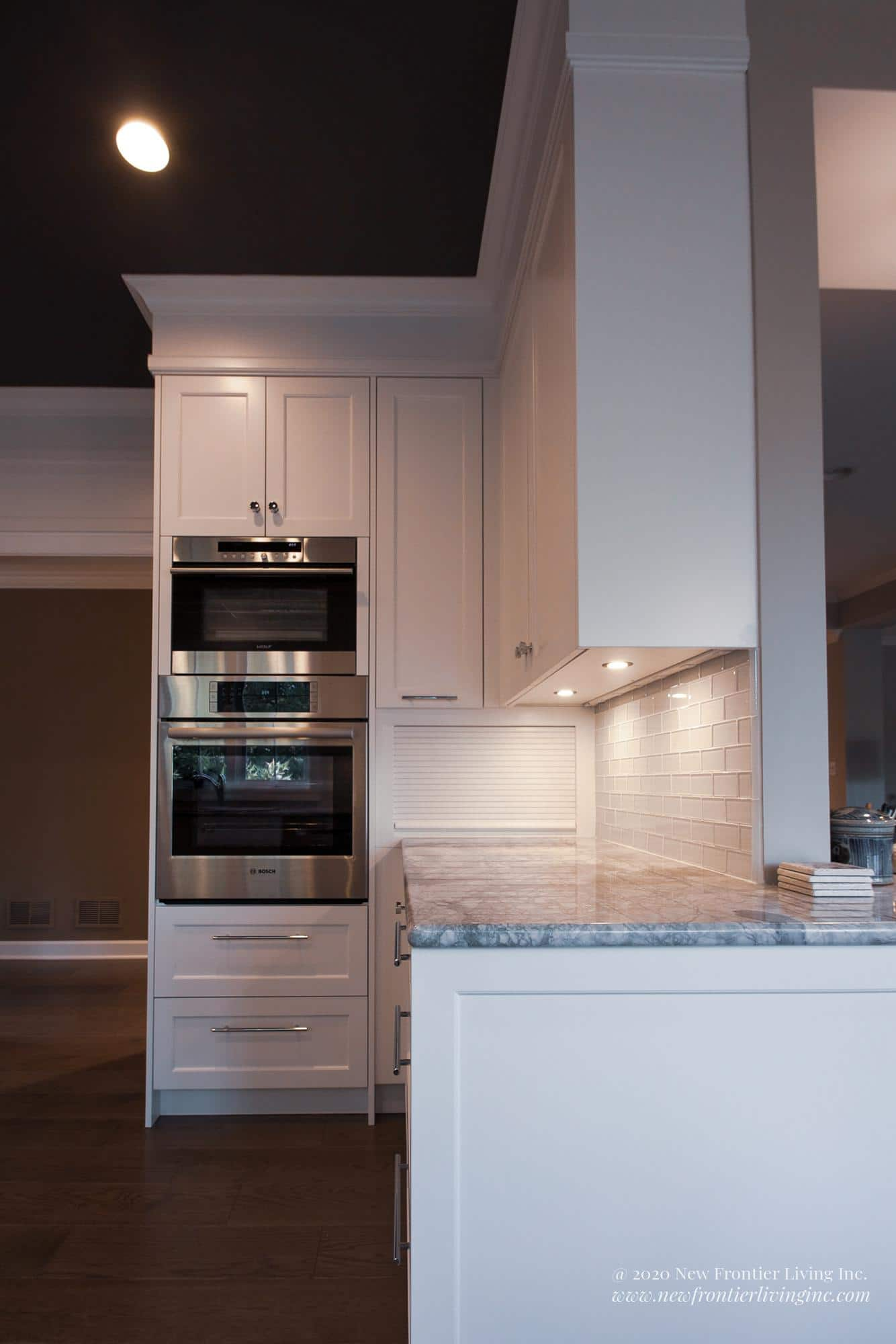 White kitchen cabinetry with handles, oven and microwave front