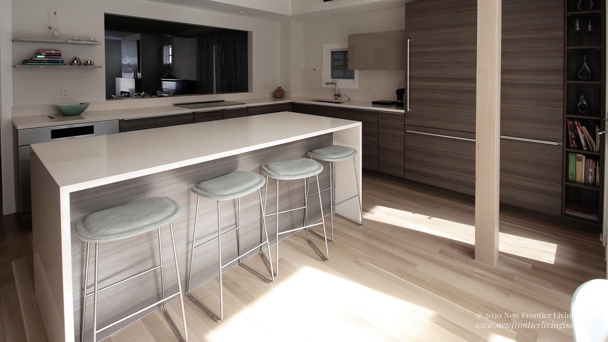 Light gray and brown PoggenPohl kitchen with waterfall kitchen island
