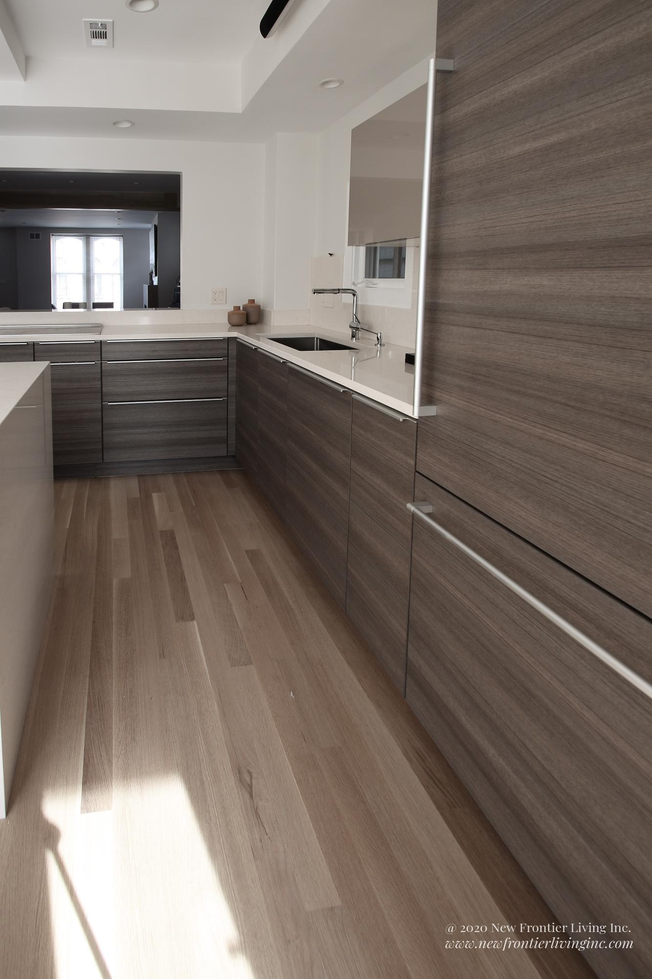 Dark brown and tall kitchen cabinets on the entire wall, sink on the right
