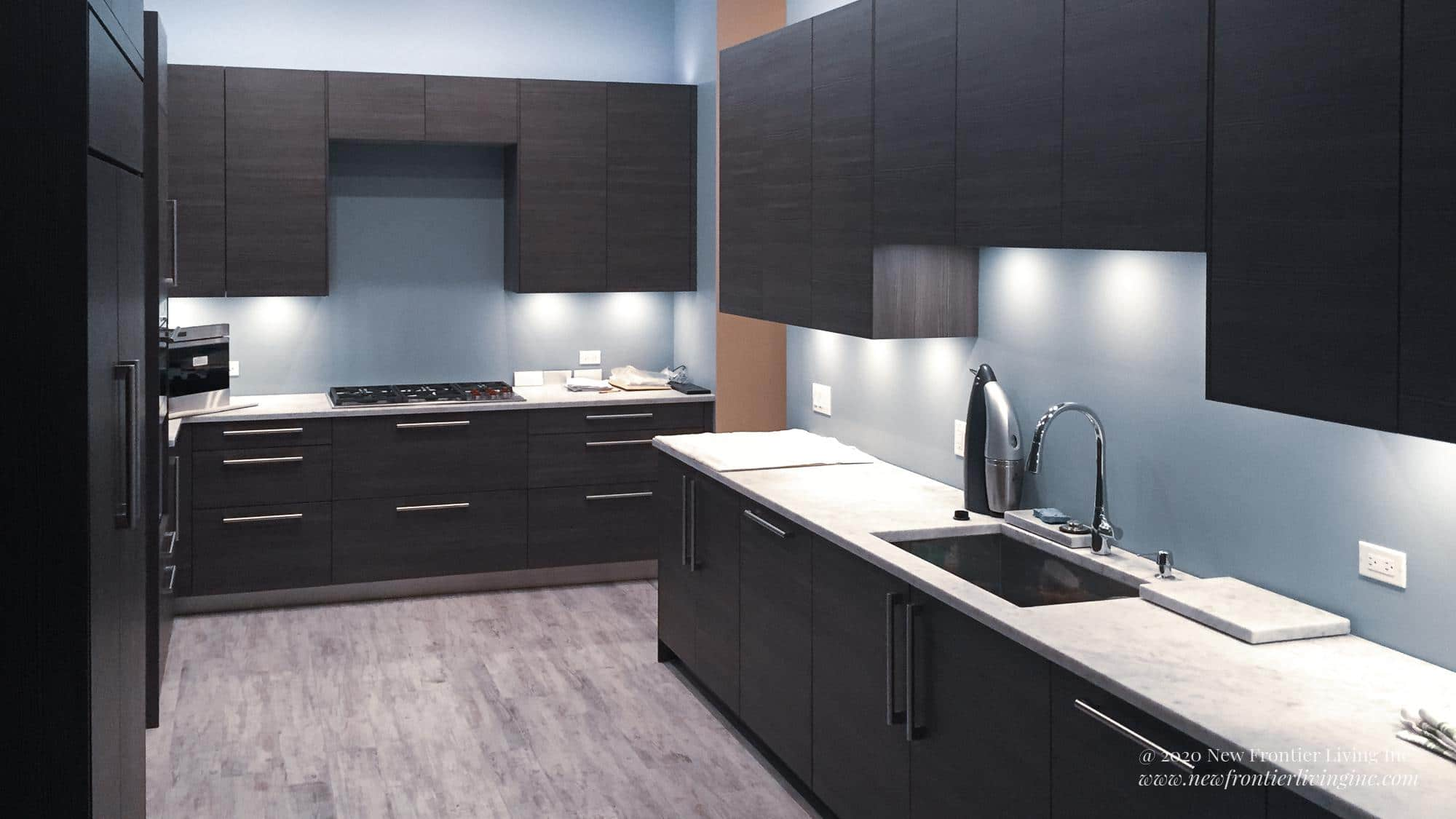 Black kitchen cabinetry and white countertop and light gray floor