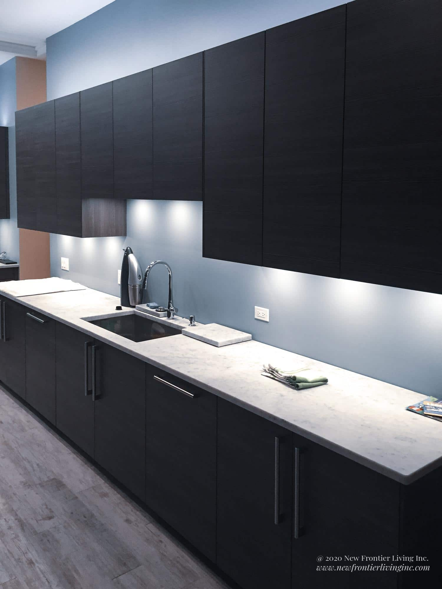 Black kitchen cabinetry and white countertop with one large sink and LED lighting