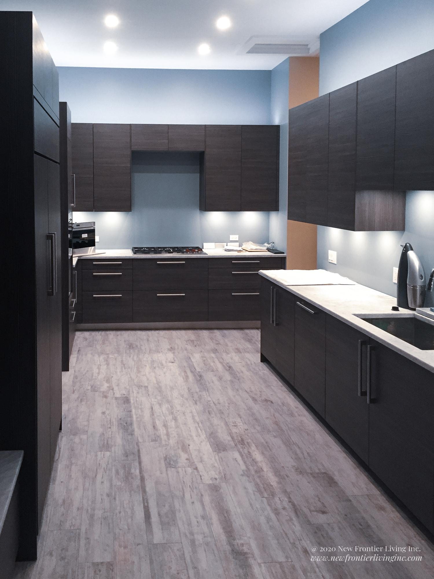 Black kitchen cabinetry and white countertop and light gray floor long view