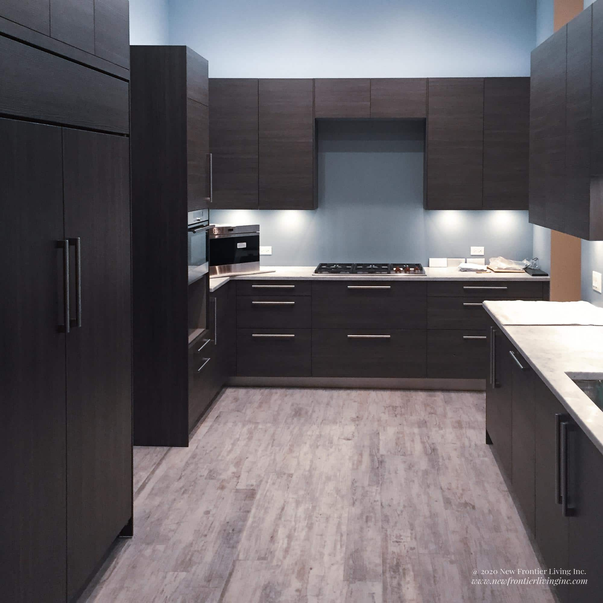 Black kitchen cabinetry and white countertop and light gray floor, large cabinets and pantries