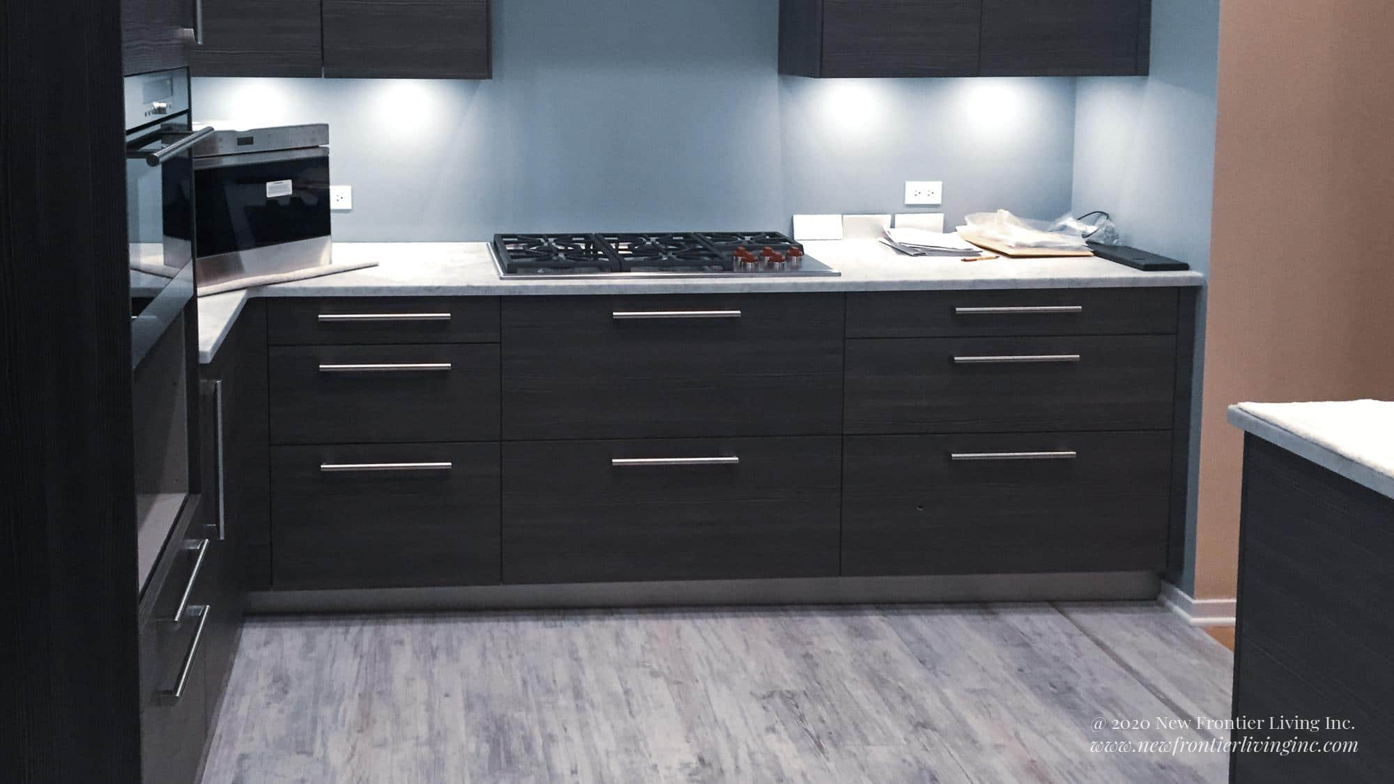 Black kitchen cabinetry and white countertop with range cooktop, microwave on the left