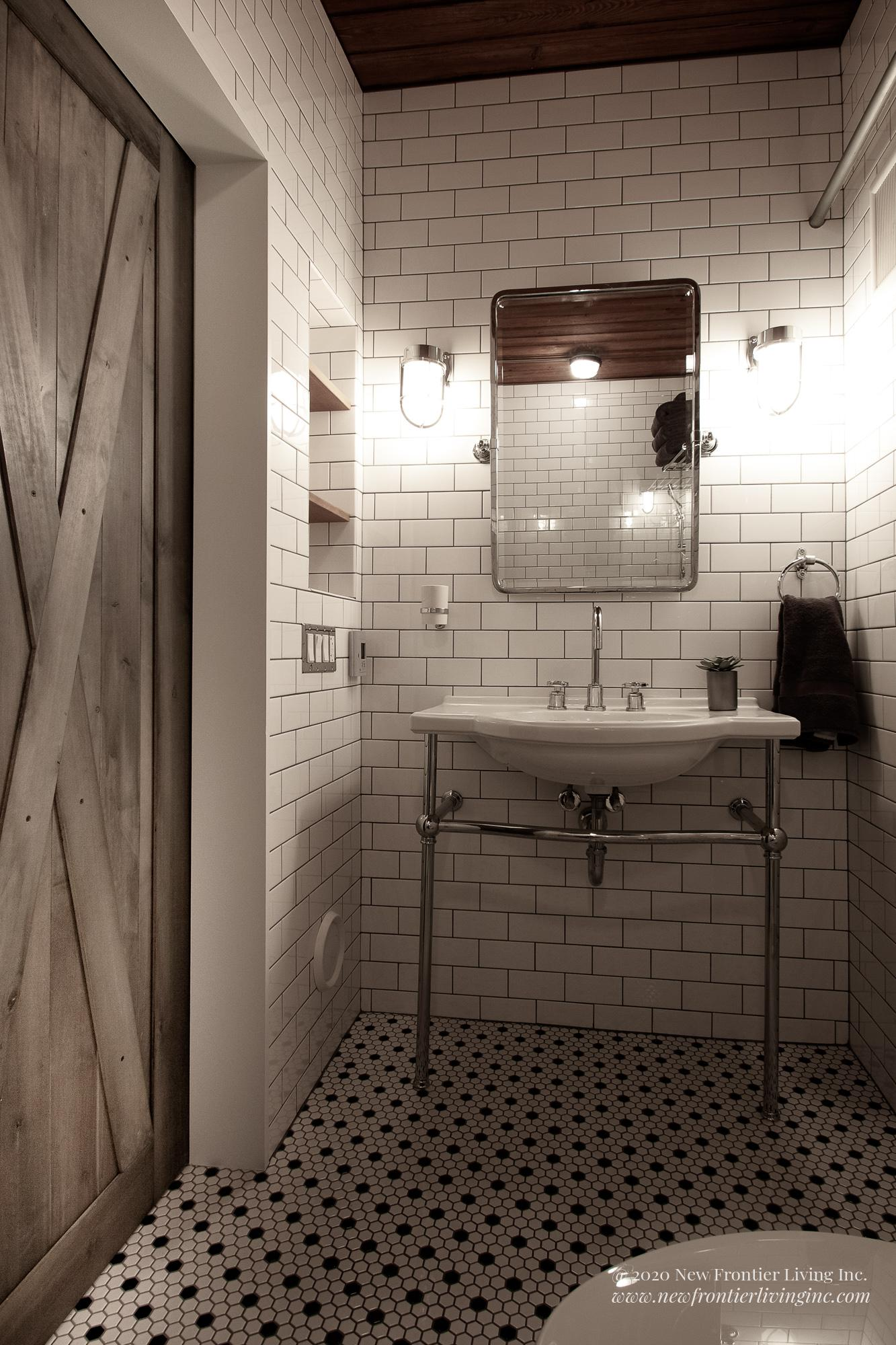Traditional white ceramic bathroom with console sink and barn door on the left
