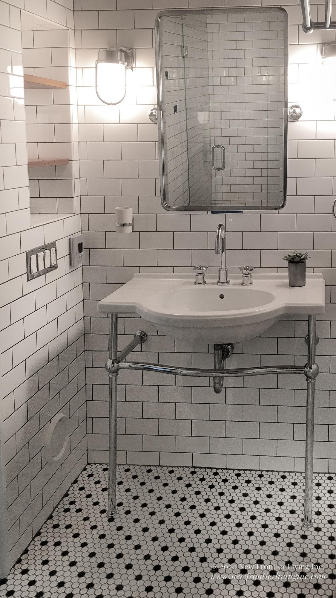 Traditional white ceramic bathroom with white and black floor tiles and console sink and a mirror