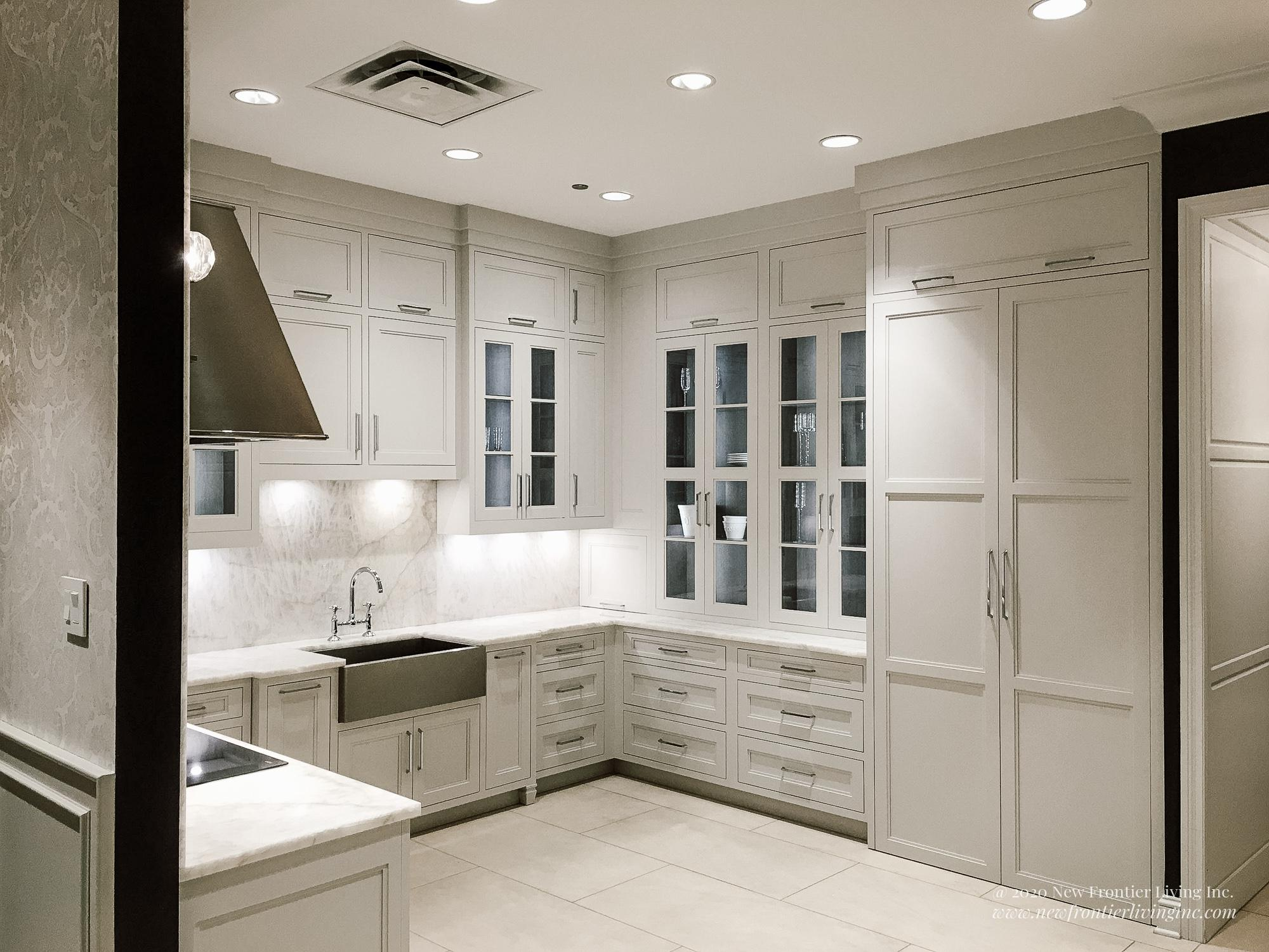 Traditional cream kitchen with silver hood and cooktop and farmhouse sink