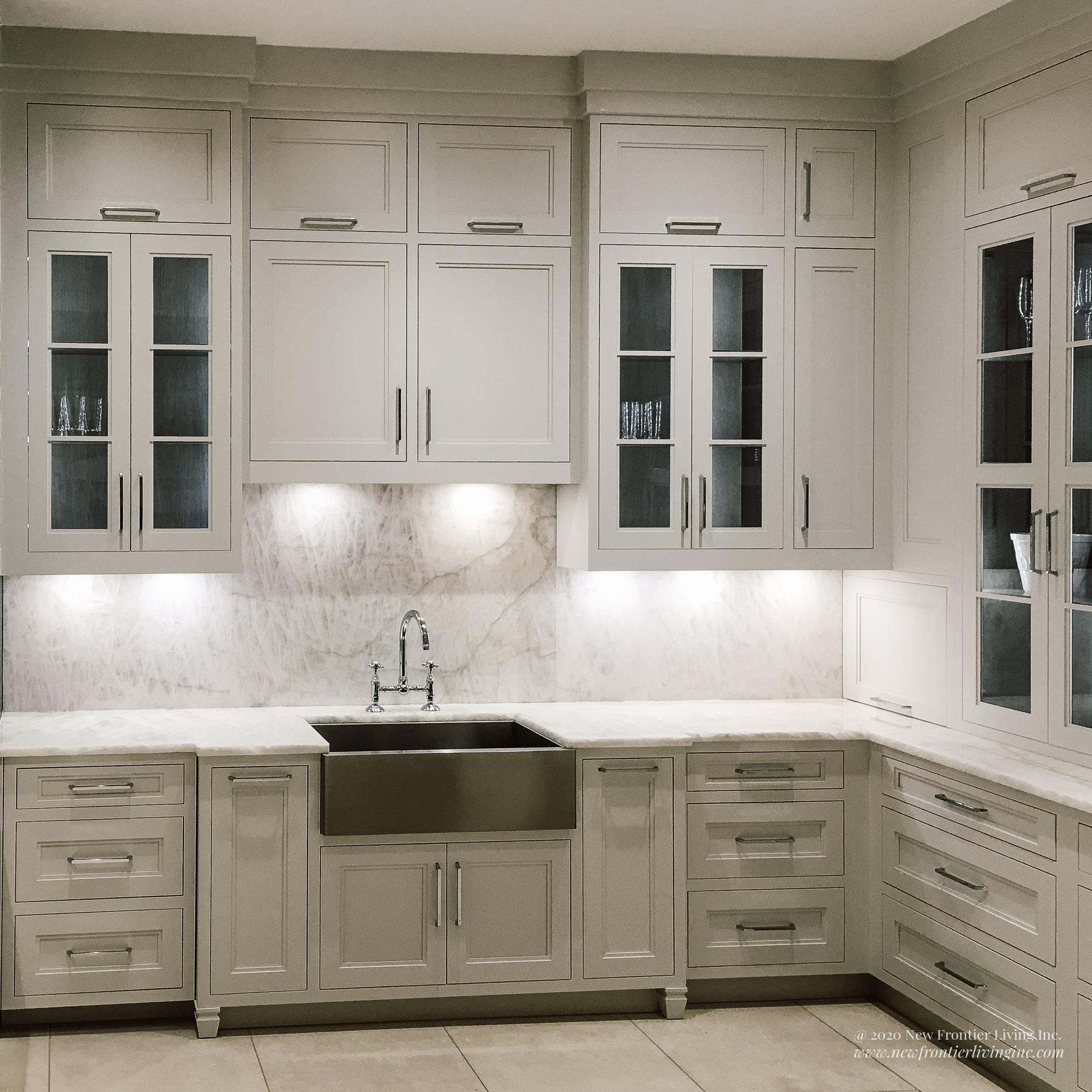 Traditional cream kitchen with silver handles and farmhouse sink and glass upper cabinetry